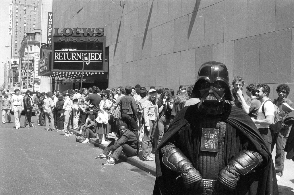 """Star Wars"" fan Danny Fitzgerald of Staten Island, in Darth Vader costume, poses in front of Loews Astor Plaza movie theater in Times Square in New York, May 25, 1983, where fans are lined up for the premiere of ""  The Return of the Jedi,""   the third in a series of the ""Star Wars"" saga. (AP Photo/Dave Pickoff)"
