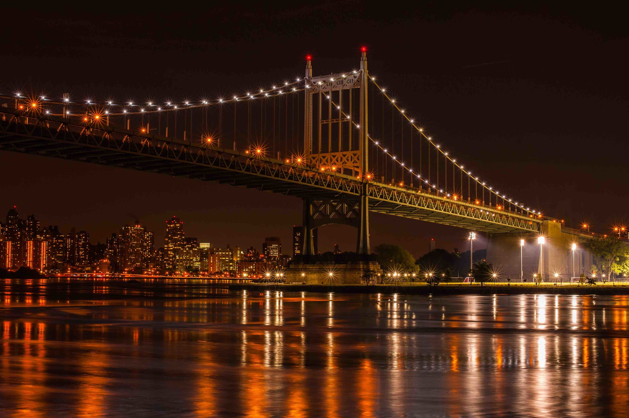 Astoria Park, Triborough Bridge, and Manhattan skyline reflecting on the East River waters