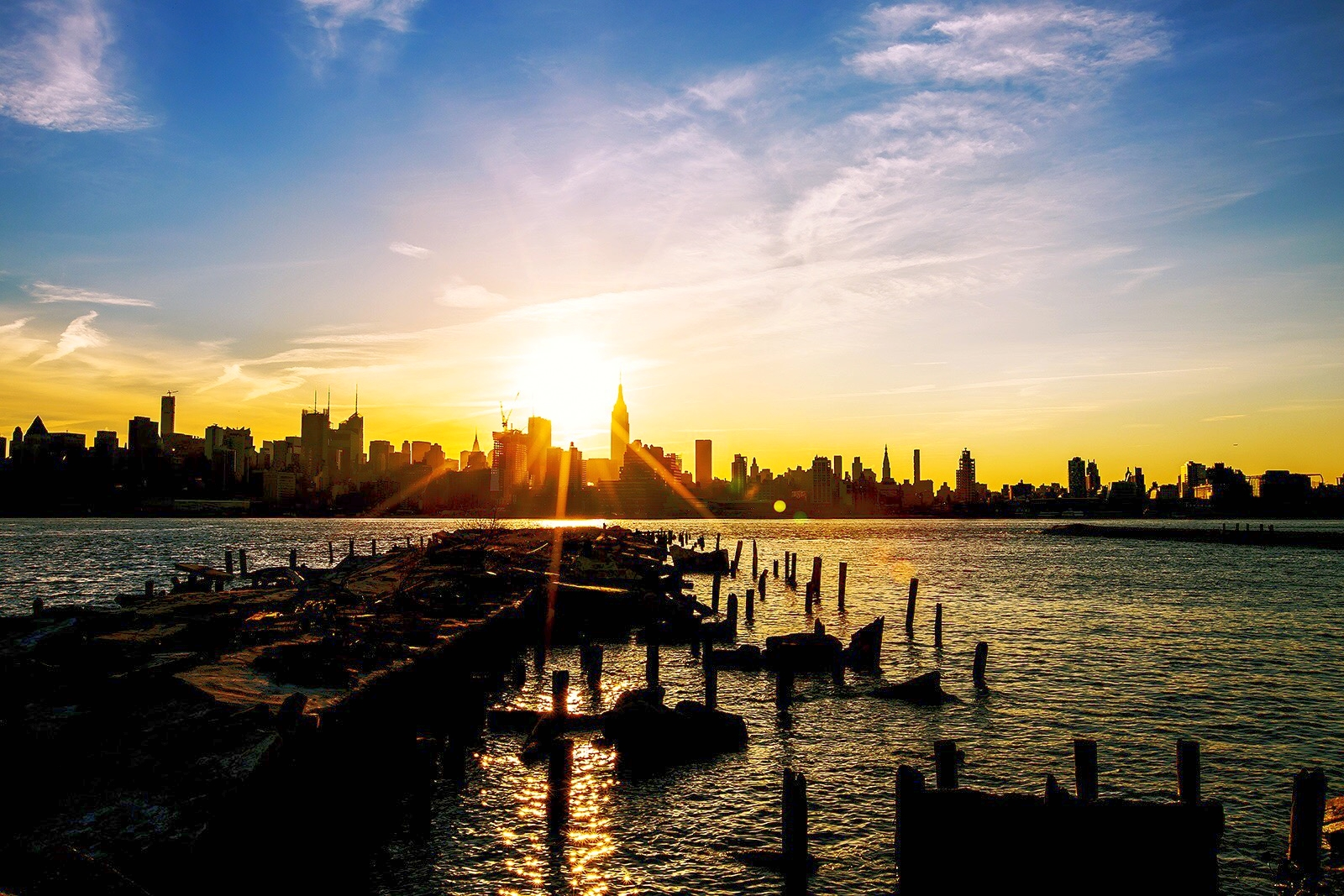 Manhattan skyline and the sun rising – seen from Hoboken at the Hudson River waterfront
