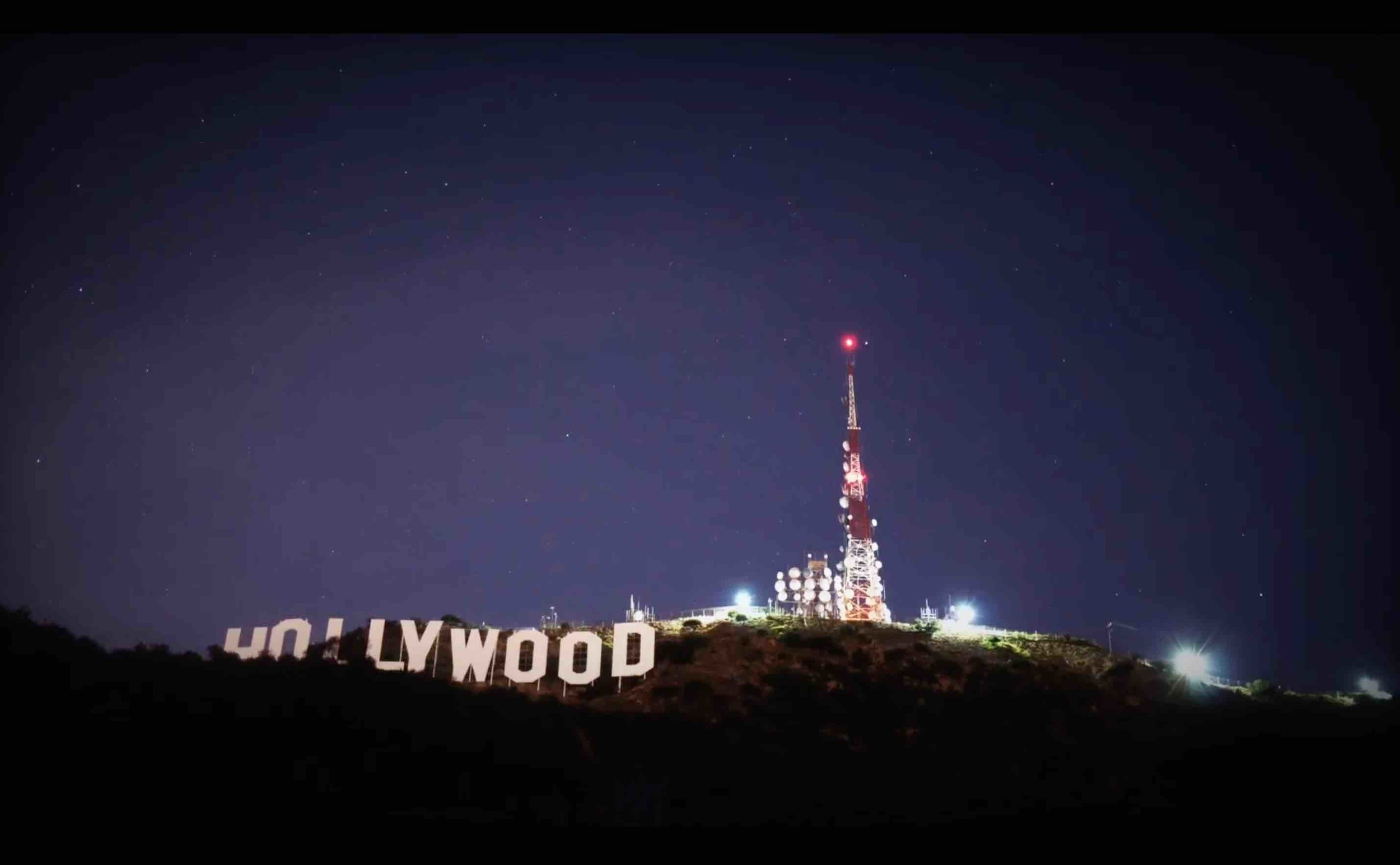 "HOLLYWOOD   is spelled out in 45-foot-tall (14 m) white capital letters and is 350 feet (110 m) long. It was originally created in 1923 as an advertisement for a local real estate development, but it garnered increasing recognition after the sign was left up. The sign was a frequent target of pranks and vandalism, but it has since undergone restoration, including the installation of a security system to deter vandalism. The sign is protected and promoted by The Trust For Public Land, a nonprofit organization, while its site and the surrounding land are part of Griffith Park.  From the ground, the contours of the hills give the sign a ""wavy"" appearance, as reflected in the Hollywood Video logo, for example. When observed at a comparable altitude, the letters appear nearly level.  The sign makes frequent appearances in popular culture, particularly in establishing shots for films and television programs set in or around Hollywood. Signs of similar style, but spelling different words, are frequently seen as parodies. The sign inspired Los Angeles artist Ed Ruscha who rendered it in different media."