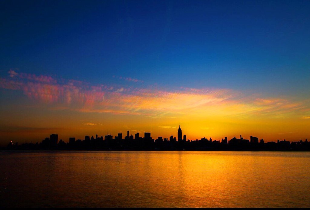 The sun rising behind Midtown Manhattan skyline