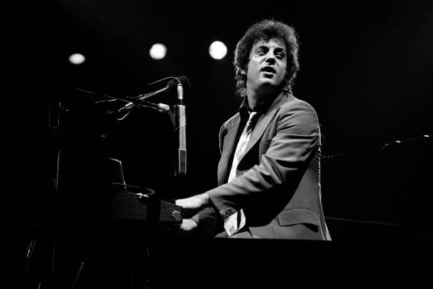 """William Martin """"Billy""""Joel (born May 9, 1949) is an American singer-songwriter and pianist. Since releasing his first hit song, """"Piano Man"""", in 1973, Joel has become the sixth best-selling recording artist and the third best-selling solo artist in the United States.His compilation album Greatest Hits Vol. 1 & 2 is one of the best-selling albums in the US. Joel had Top 40 hits in the 1970s, 1980s, and 1990s, achieving 33 Top 40 hits in the US, all of which he wrote himself. He is also a six-time Grammy Award winner who has been nominated for 23 Grammy Awards. He has sold more than 150 million records worldwide, making him one of the best-selling artists of all time"""