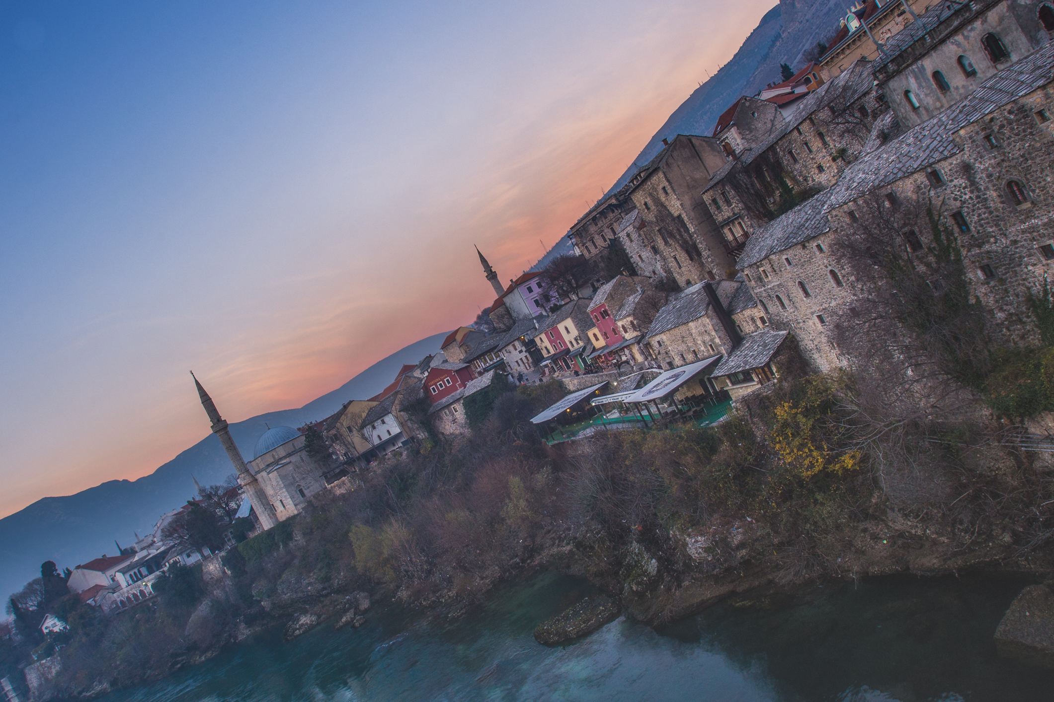 The town of Mostar, Bosnia as seen at dusk from the iconic Stari Most bridge. This place was  under siege  during the Croat-Bosniak war in the early 1990s.