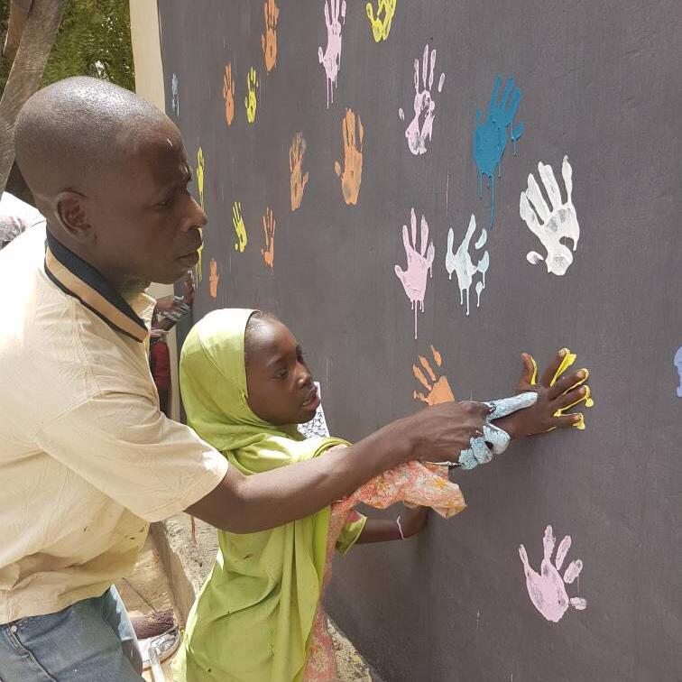 De kinderen mogen samen met de begeleiders de muur van hun leercentrum versieren. Zo voelen ze zich thuis en is het een fijne plek voor hen.
