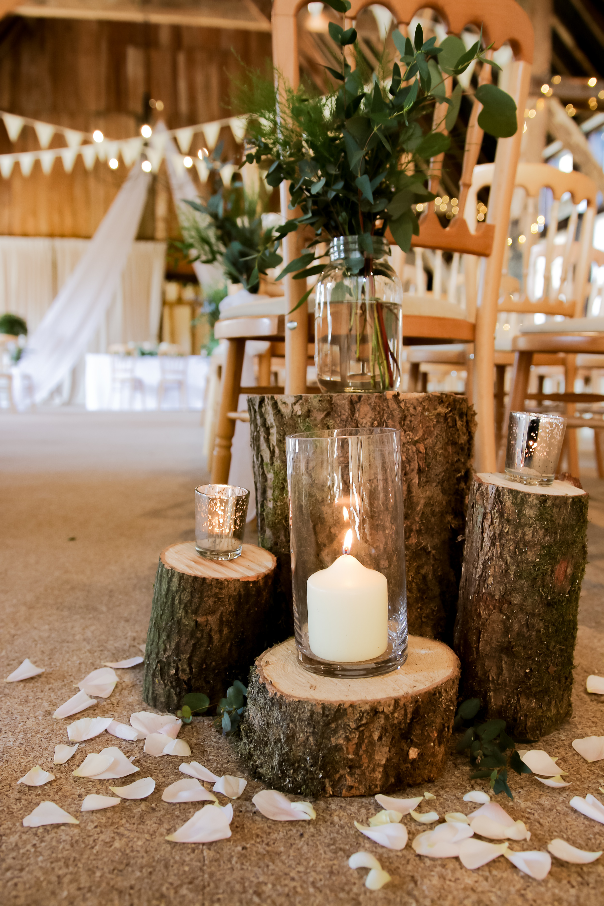 RUSTICWooden LogsAisle Decor - Includes 4 wooden stumps in varying sizes with 1 hurricane vase and candles with 2 tea lights and holders and greenery for the top. Prices are £40.00 each or £70.00 for both sides.