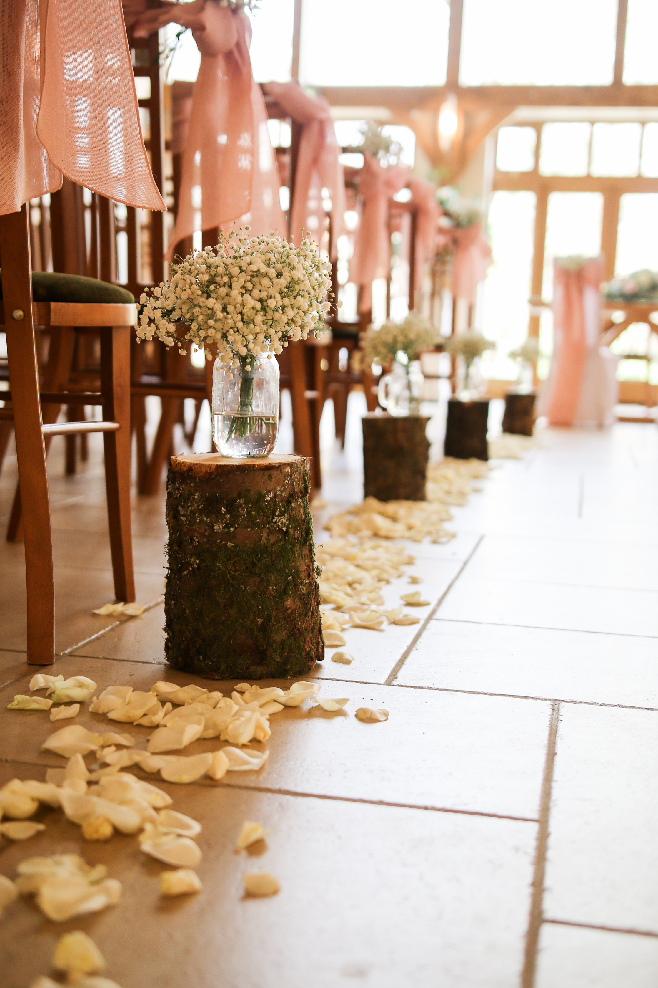 Log stumps With flowerVases - A beautiful way to add a rustic touch to your aisle, with flower vases included, created in keeping with your wedding coloursThese are approx £20.00 each or£15.00 each with gyp flowersor greenery. Petals not included in pricing