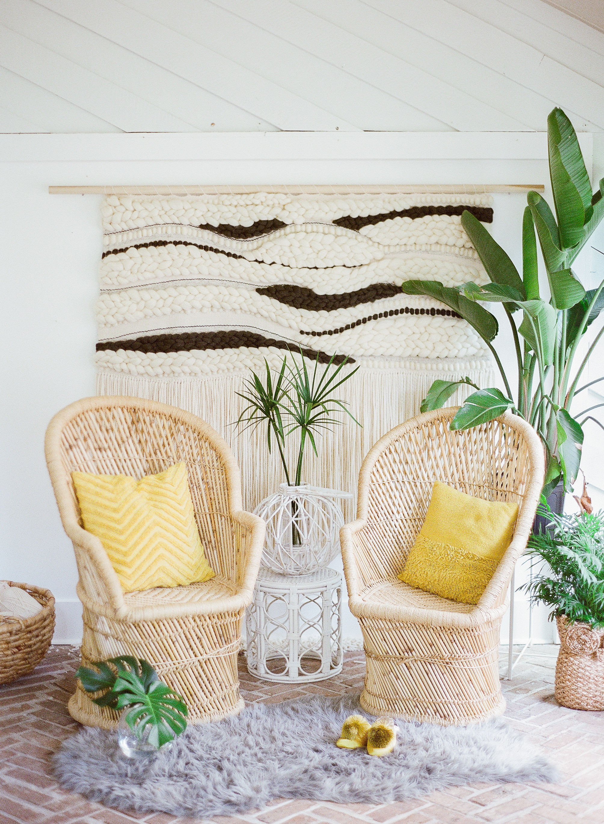 Palm beach Florida themed decor with woven wall hanging and peacock chairs