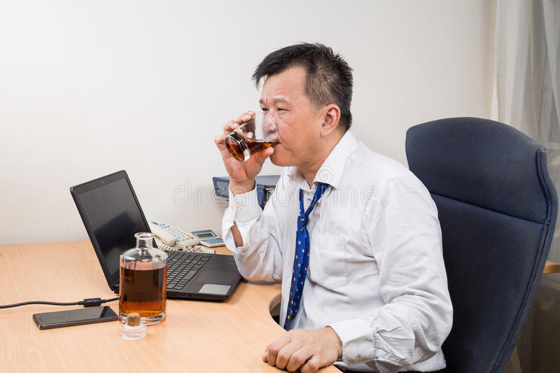 frustrated-stressful-asian-manager-drinking-hard-liquor-o-business-office-65161951.jpg