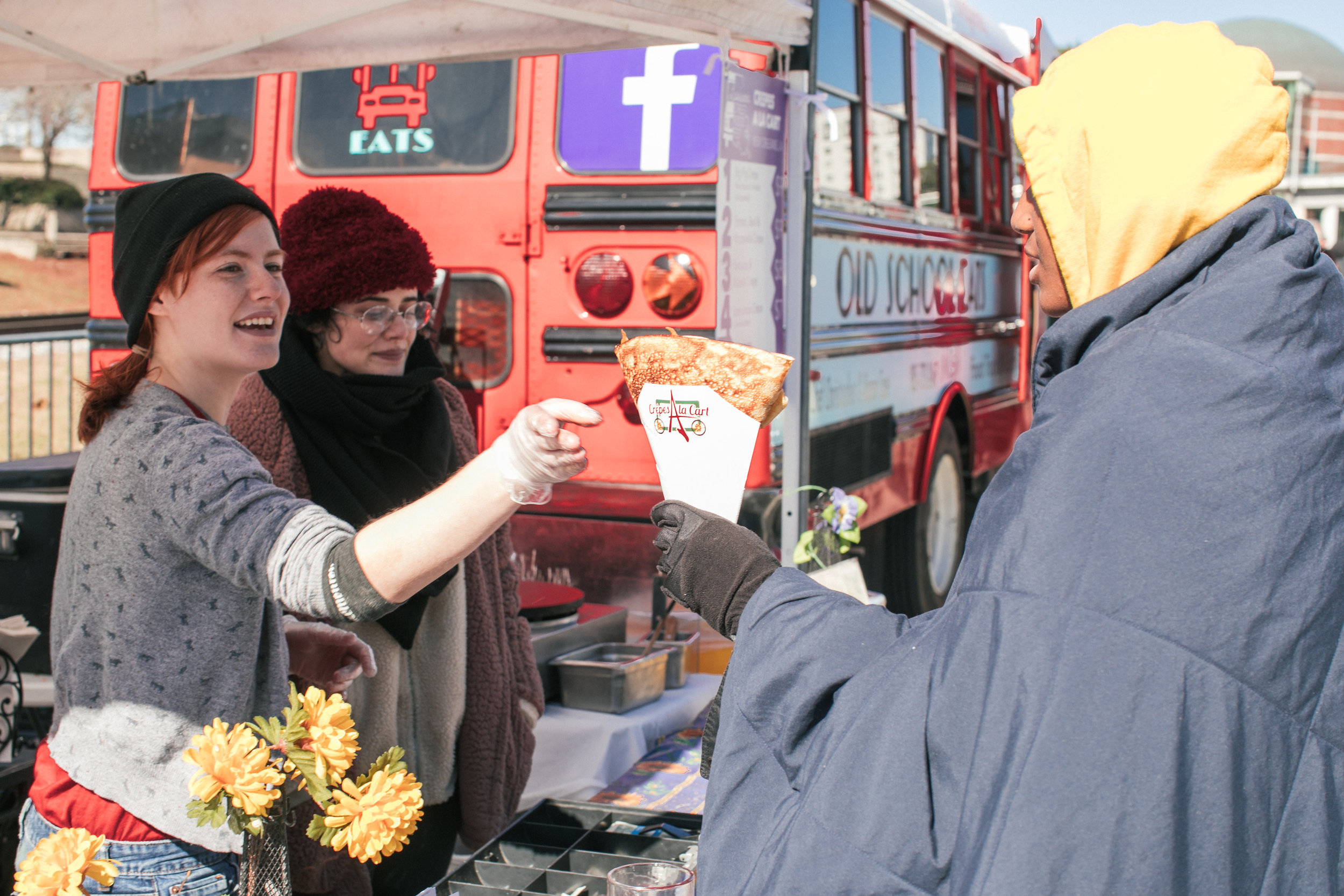 The team at NOLA-based Crepes a la Cart hands off one of their sweet or savory treats to a heavily bundled customer.  OA