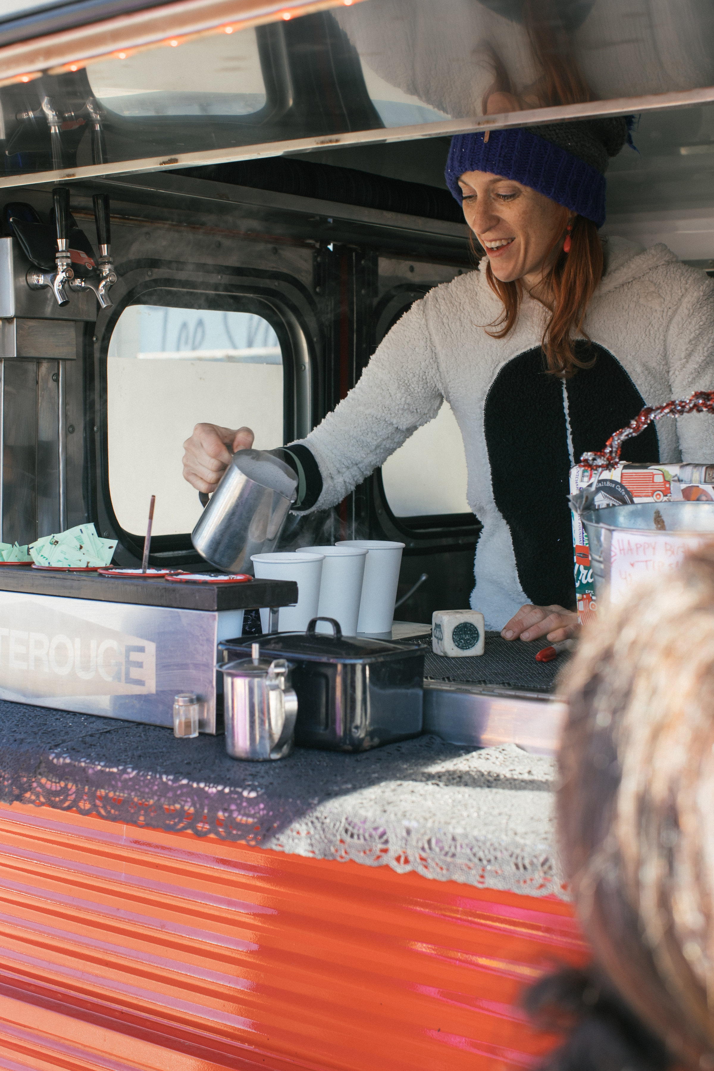 Julie of NOLA-based Petite Rouge Coffee wears a onesie and pours specialty espresso drinks from her vintage 1970 Citroen H-Van.  OA