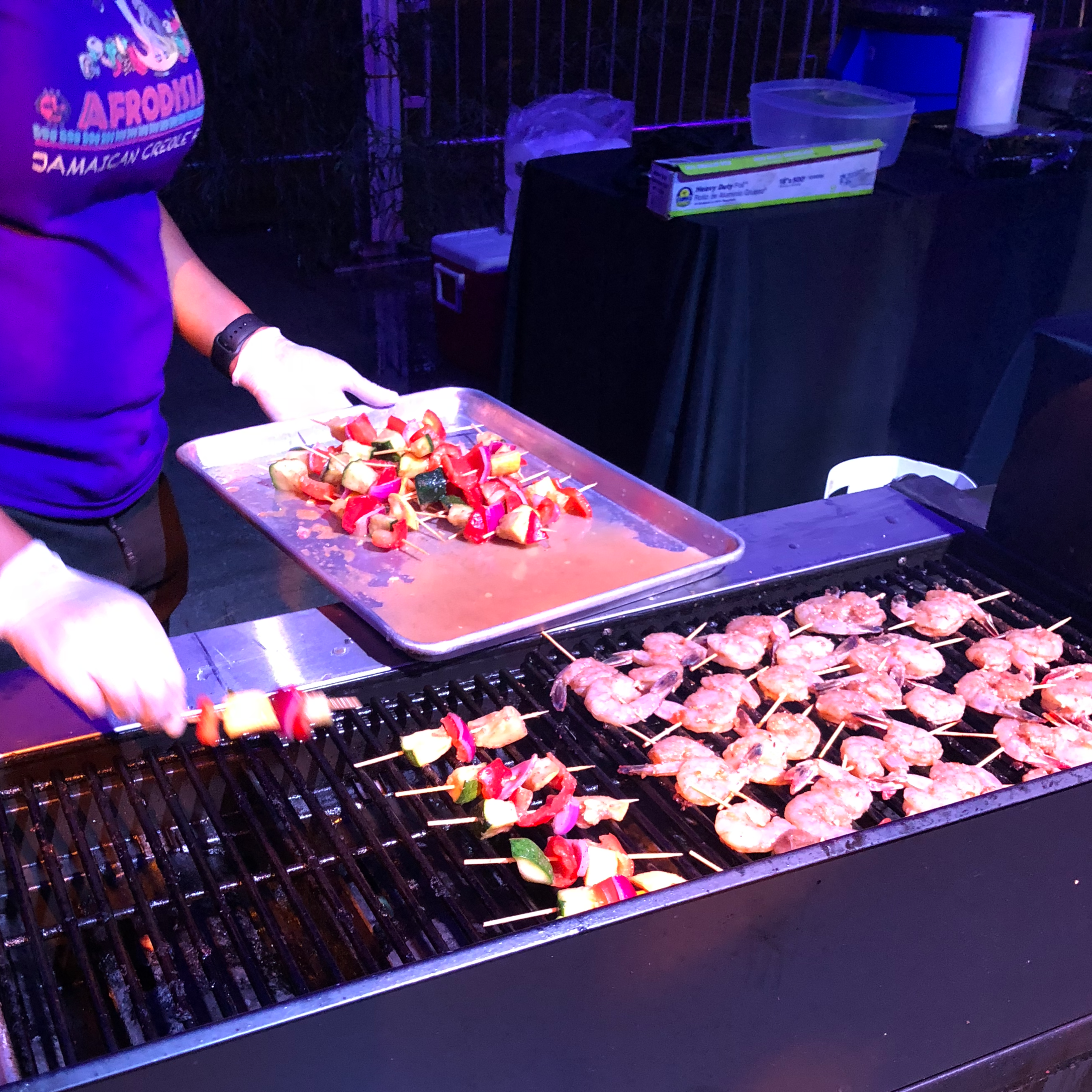 Shaka of Afrodisiac placing skewers on the grill