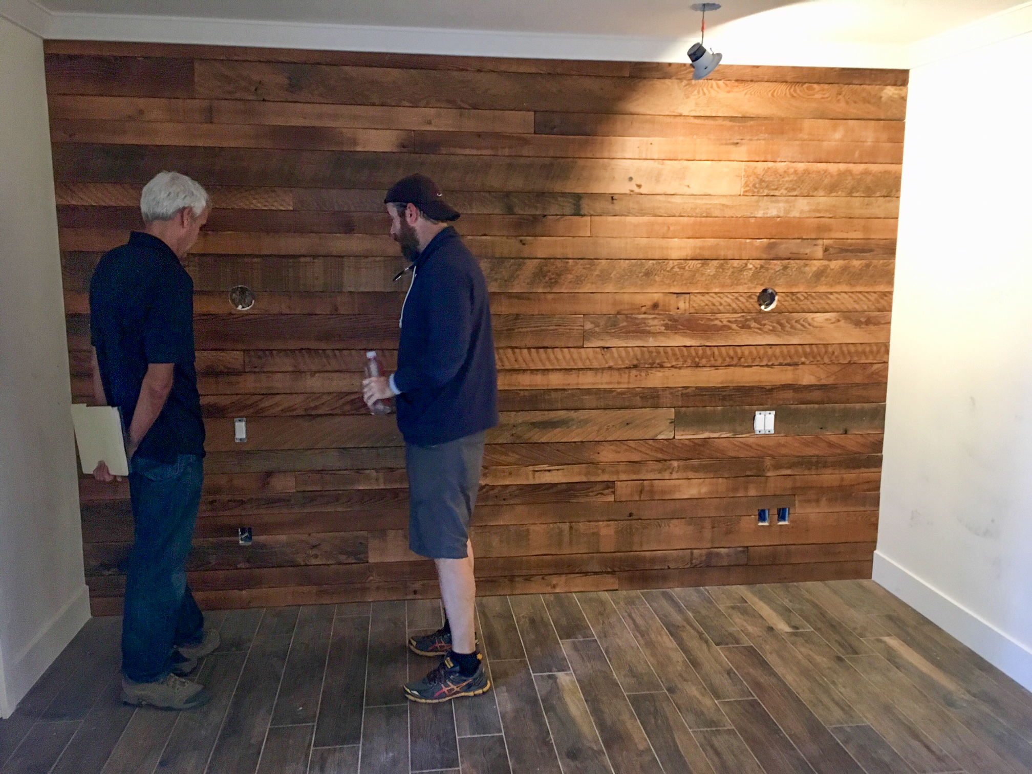 "This is the project manager and client in his new bedroom in San Diego... Guys, check out this combo of finishes. 😍 Durable, wood look-alike floor tiles with a real reclaimed wood wall. The wall will serve as the ""headboard"". 🛏 Can't wait to see it with the wall sconces, panel bed, and new rugs. This place is gonna be lookin' goooood. 😁  Need help with the finishes in your home? Message me! 👋🏻  Also, if you're looking for a project manager in SD, message me. Ed Earl is amazing. 🙌🏻 Seriously."