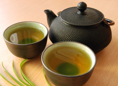 cast_iron_teapot_with_two_cups_of_green_tea.jpg