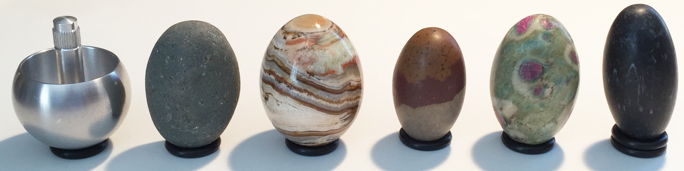 A variety of spinning objects: tippe-top; natural pebble; polished jasper stone egg; classic Lingam stone; ruby/fuschite Lingam stone; black Lingam stone. Each is about 5 cm tall.