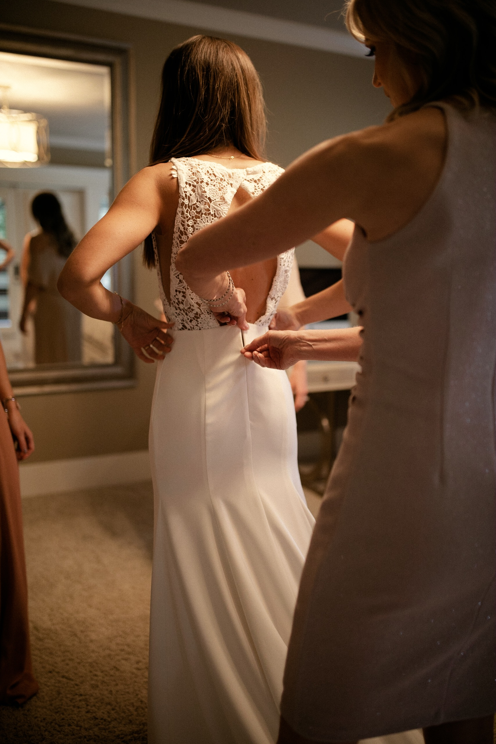 Mother of the bride zipping up bride's Sarah Seven dress