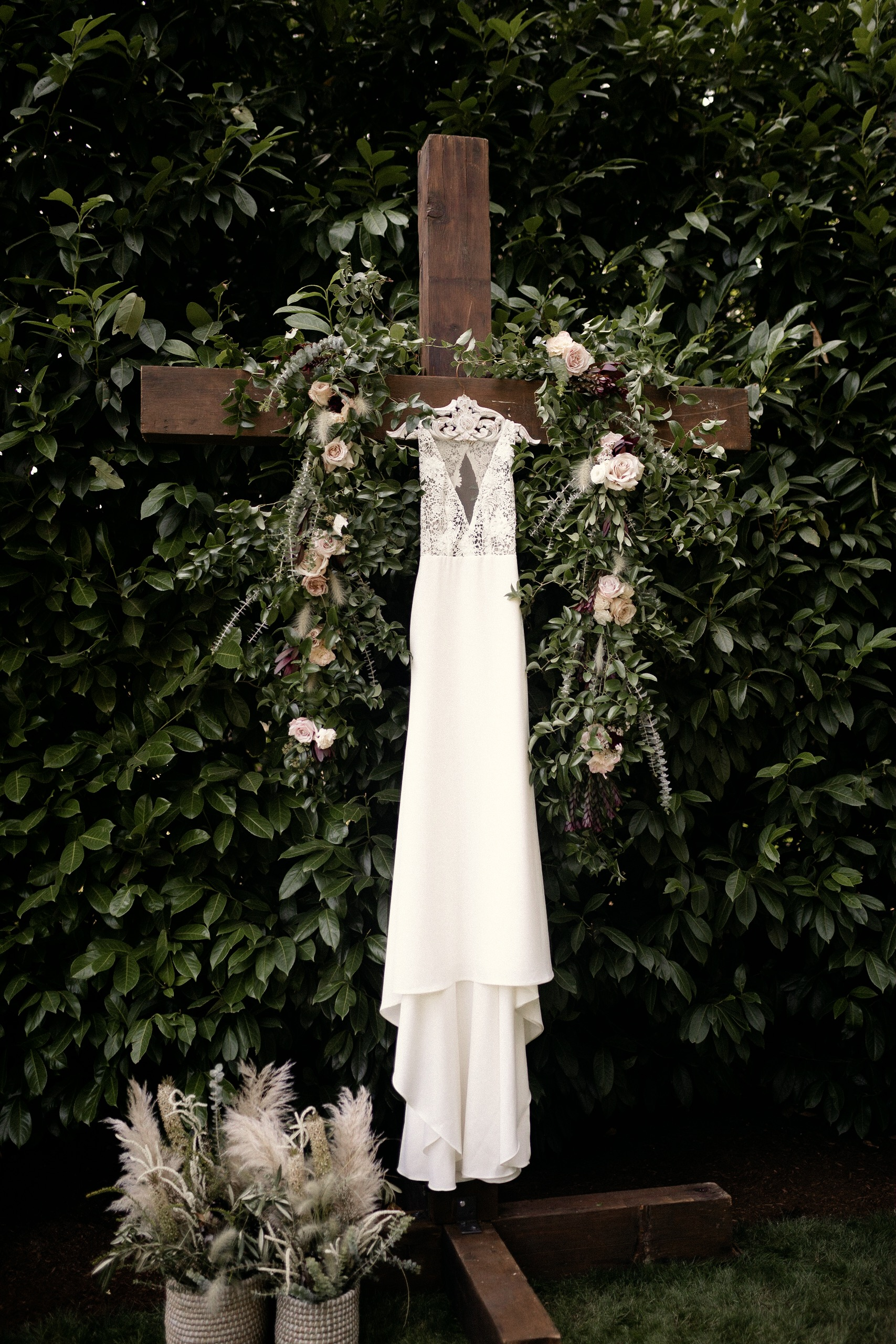Sarah Seven wedding dress hanging on cross with Brier and Ivy floral installation Portland Oregon