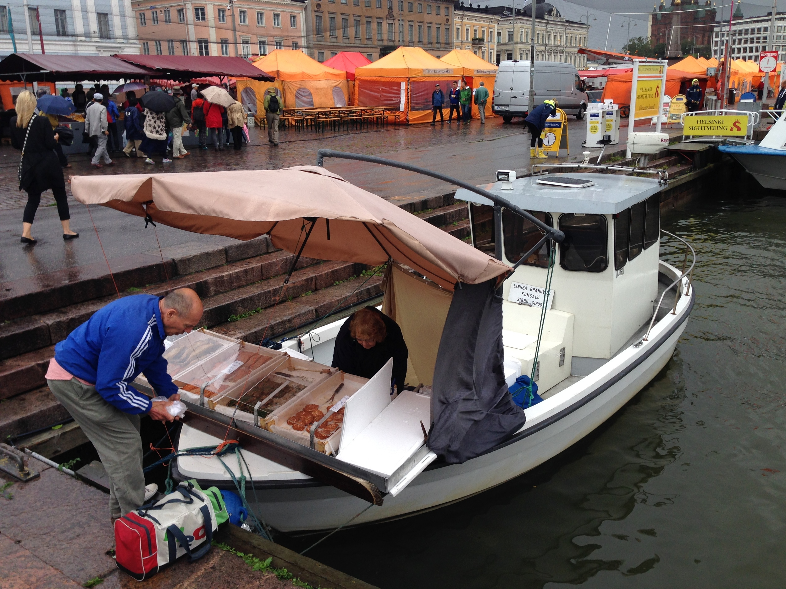 A fishmonger selling straight off the boat, while the rest of the market is visible on land in the background.