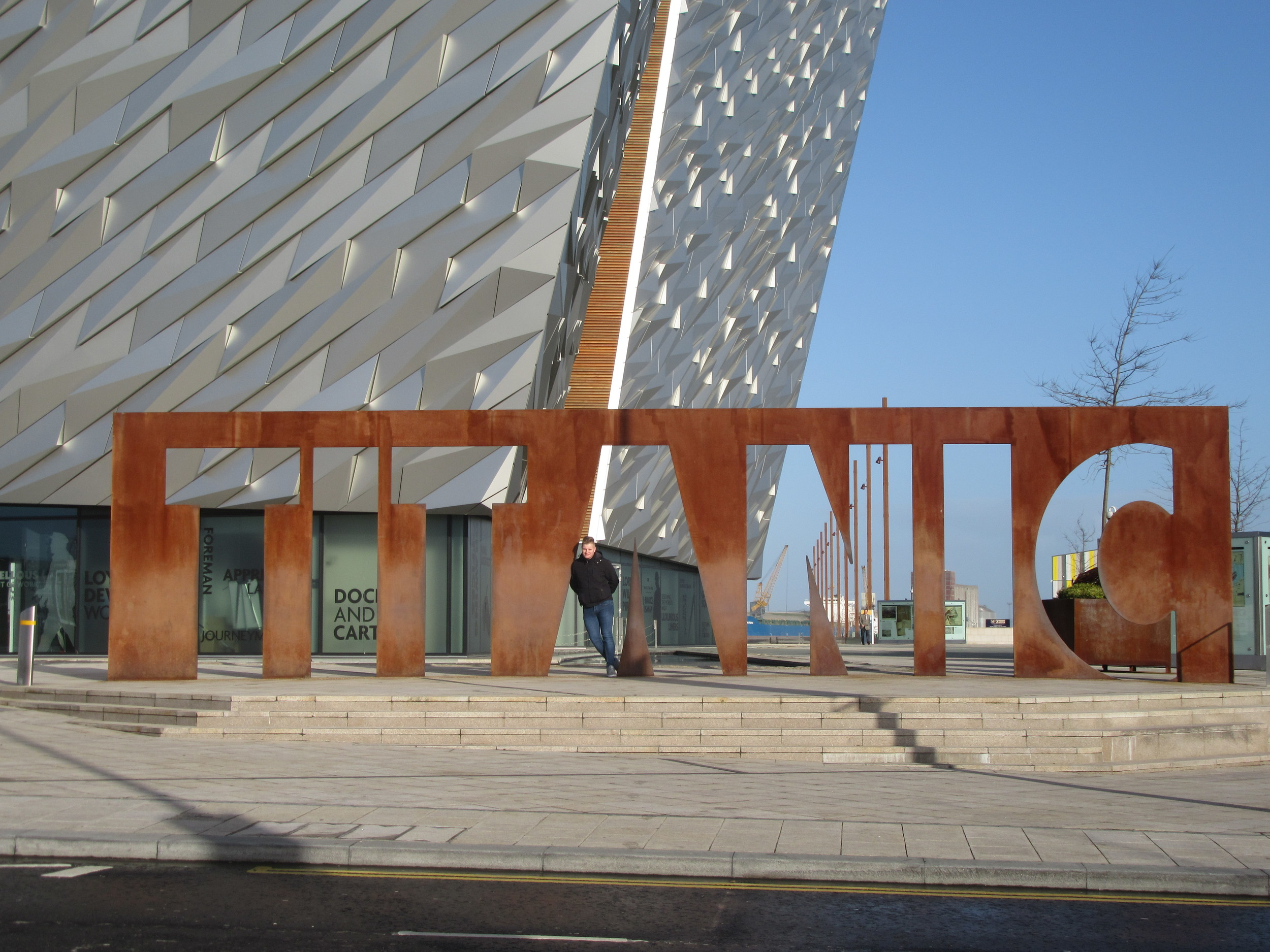 Standing outside Titanic Belfast. The building behind the sign is the same height as the ship's body.