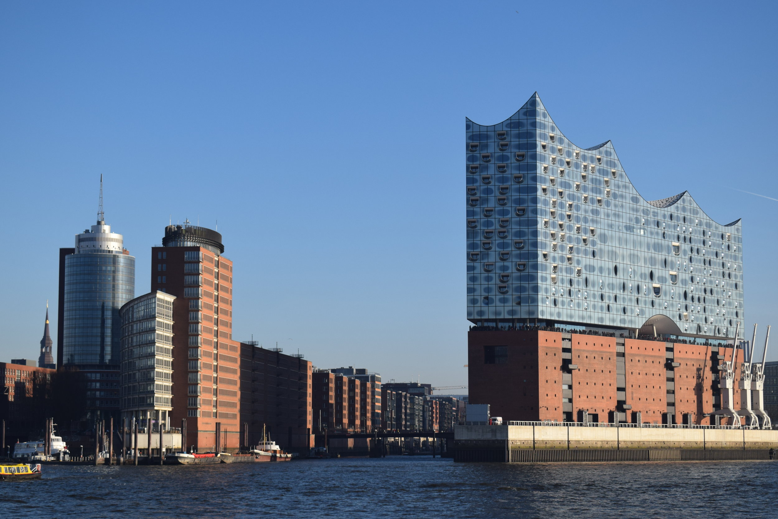 A gateway to the Speicherstadt from the River Elbe, overlooked on the right by the Elbphilharmonie - a concert hall.