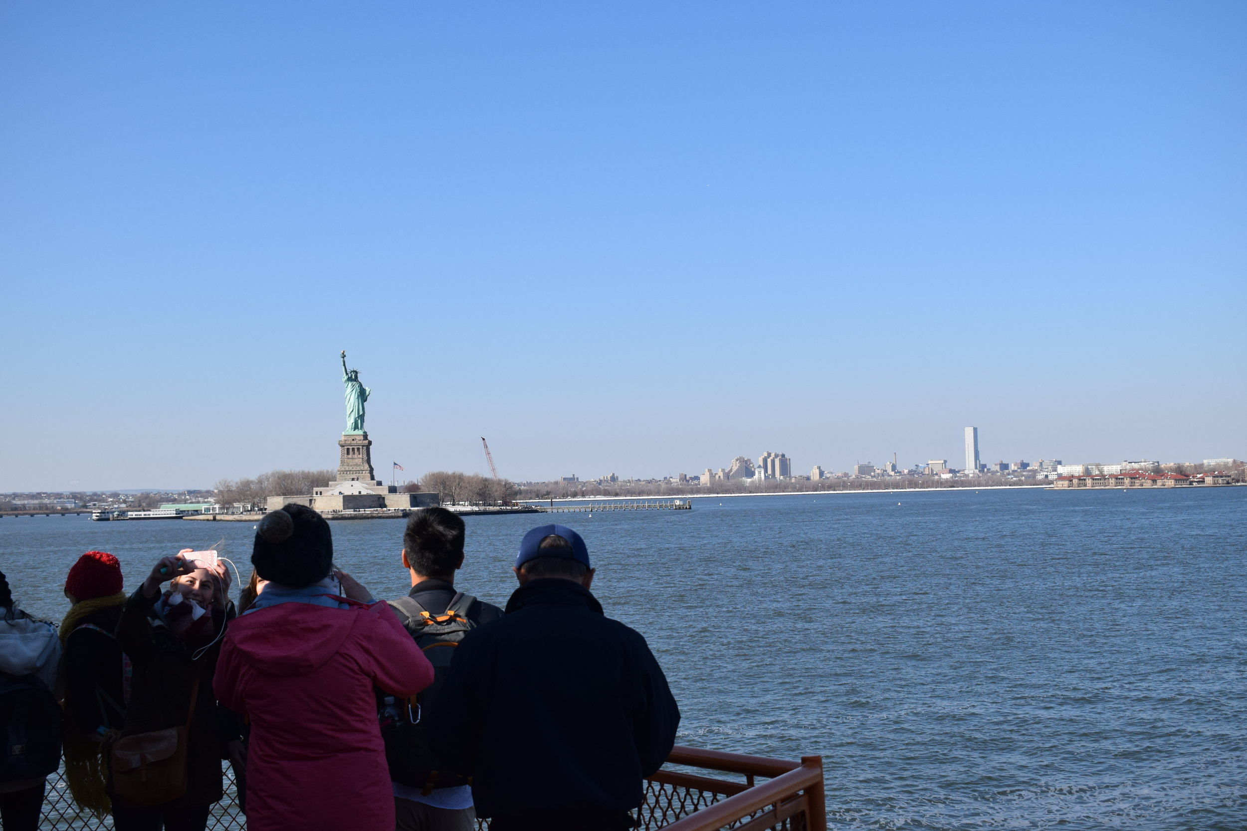 Tourists take pictures with and of the Statue of Liberty aboard the Staten Island Ferry.
