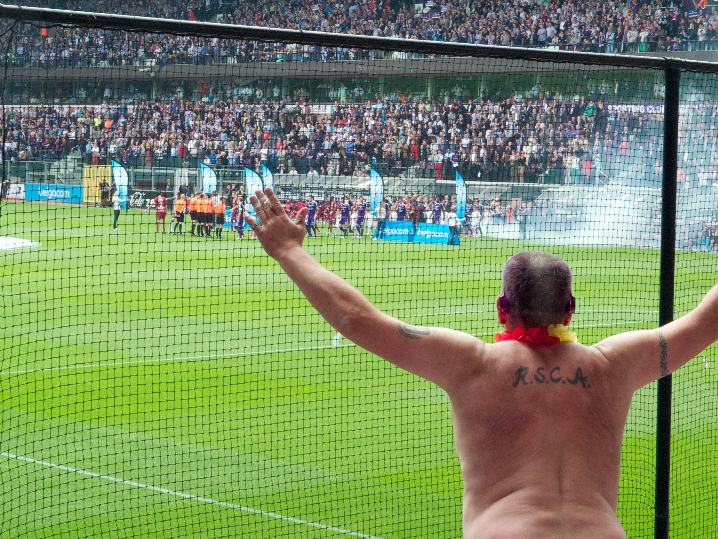 An Anderlecht fan cheers the team on from the stands as Anderlecht clinch their 32nd league title at home to Zulte Waregem in 2013. Image credit:    Sander Spek   /   Flickr