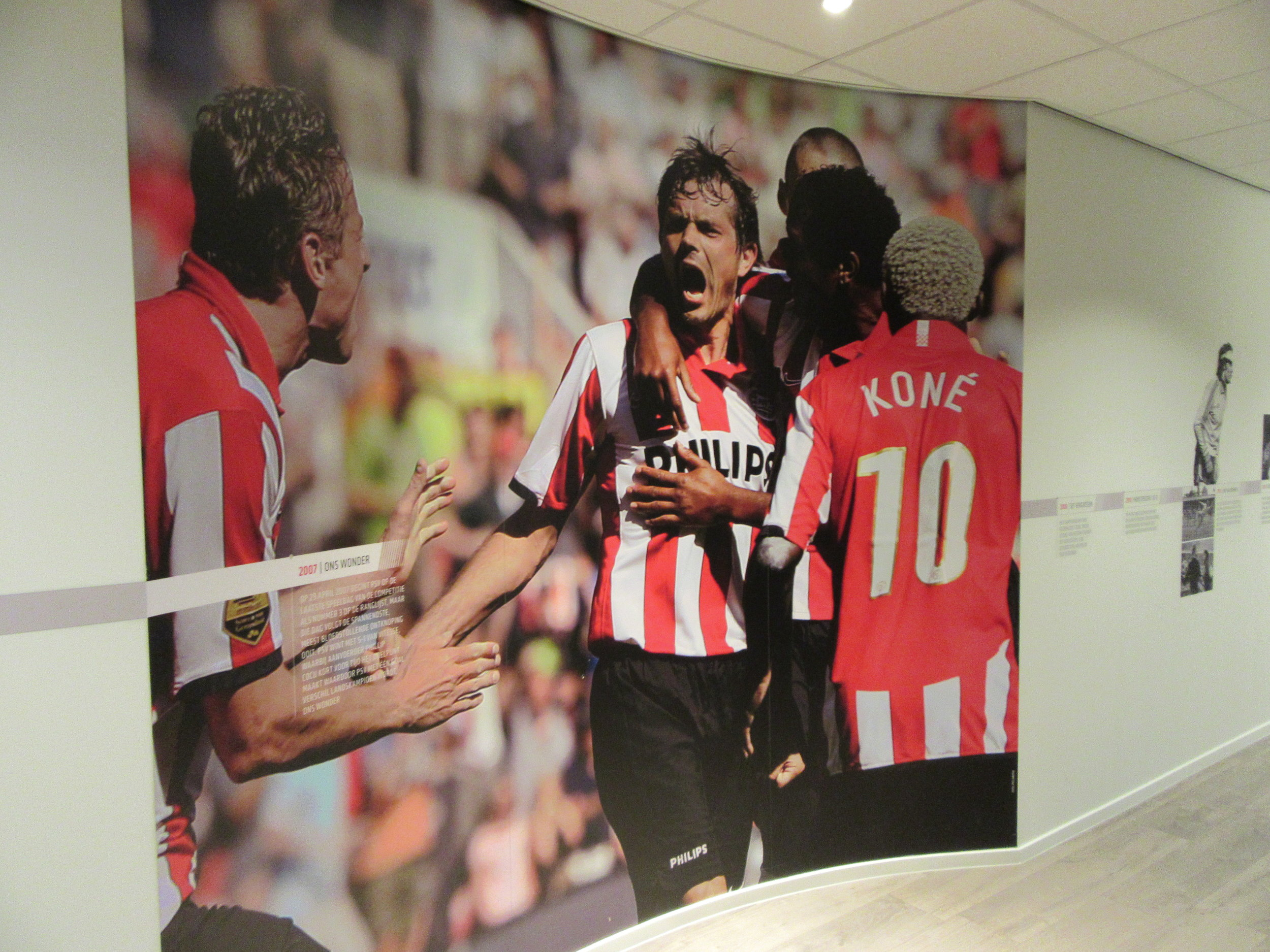 Arouna Koné celebrates with his teammates after Phillip Cocu scores in a 5-1 win over Vitesse Arnhem on the last day of the 2006-07 league campaign. PSV won the Eredivise title on goal difference, and this picture is displayed on the wall outside the press room at Philips Stadion.