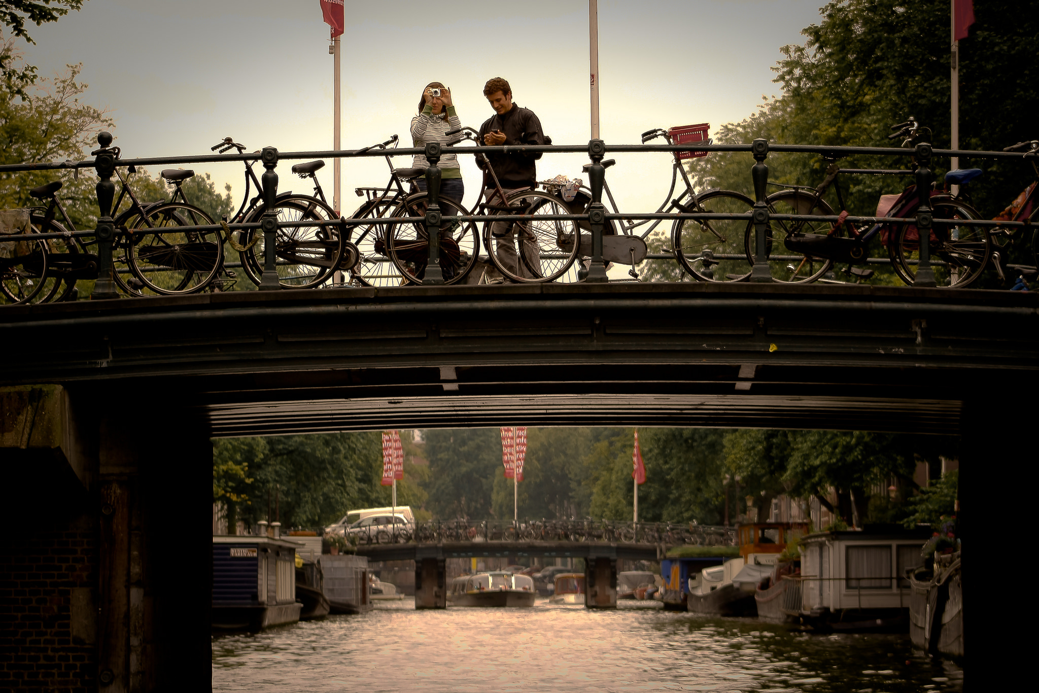 A couple snapping a photo in Amsterdam. Image credit:  Hernán Piñera / Creative Commons