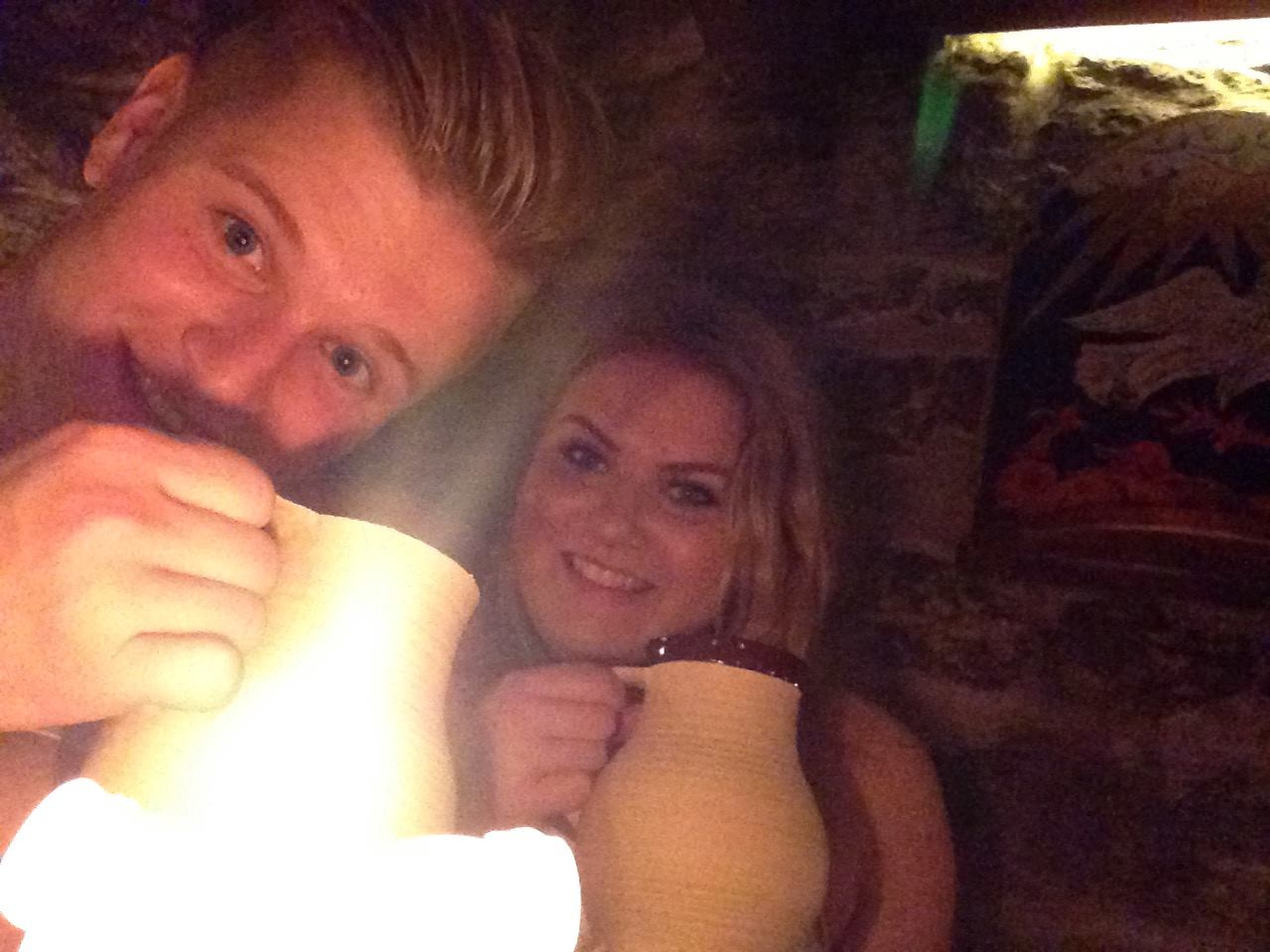 Enjoying our beer from ceramic mugs by candlelight at III Draakon.