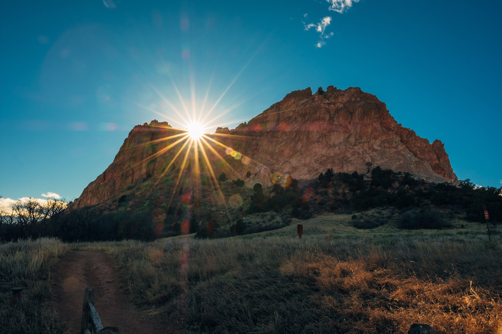 The sun peaks over rocks at Colorado's Garden of the Gods.
