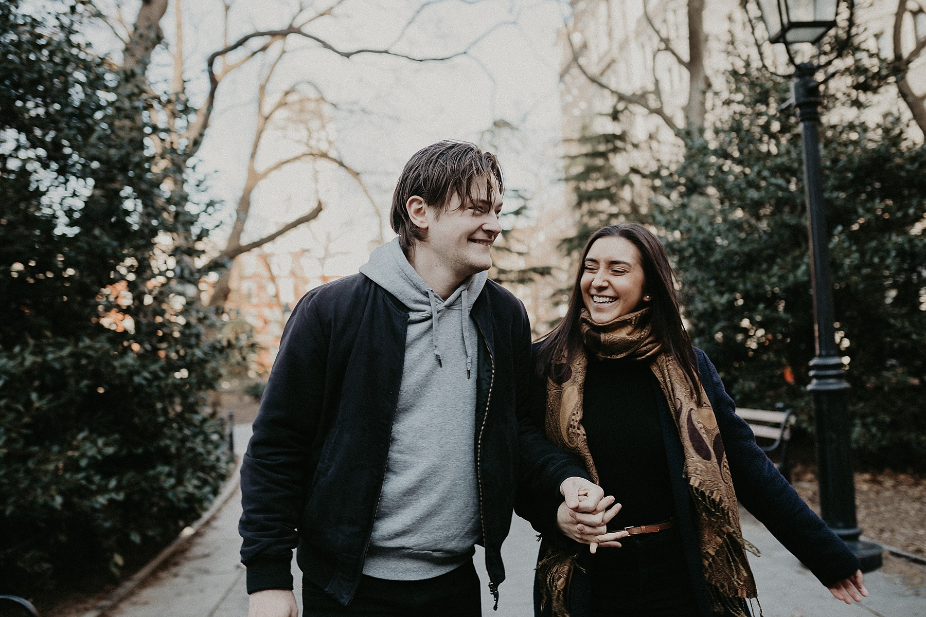 Girl looking adoringly at fiancee during engagement session in Washington Square Park in New York City, New York