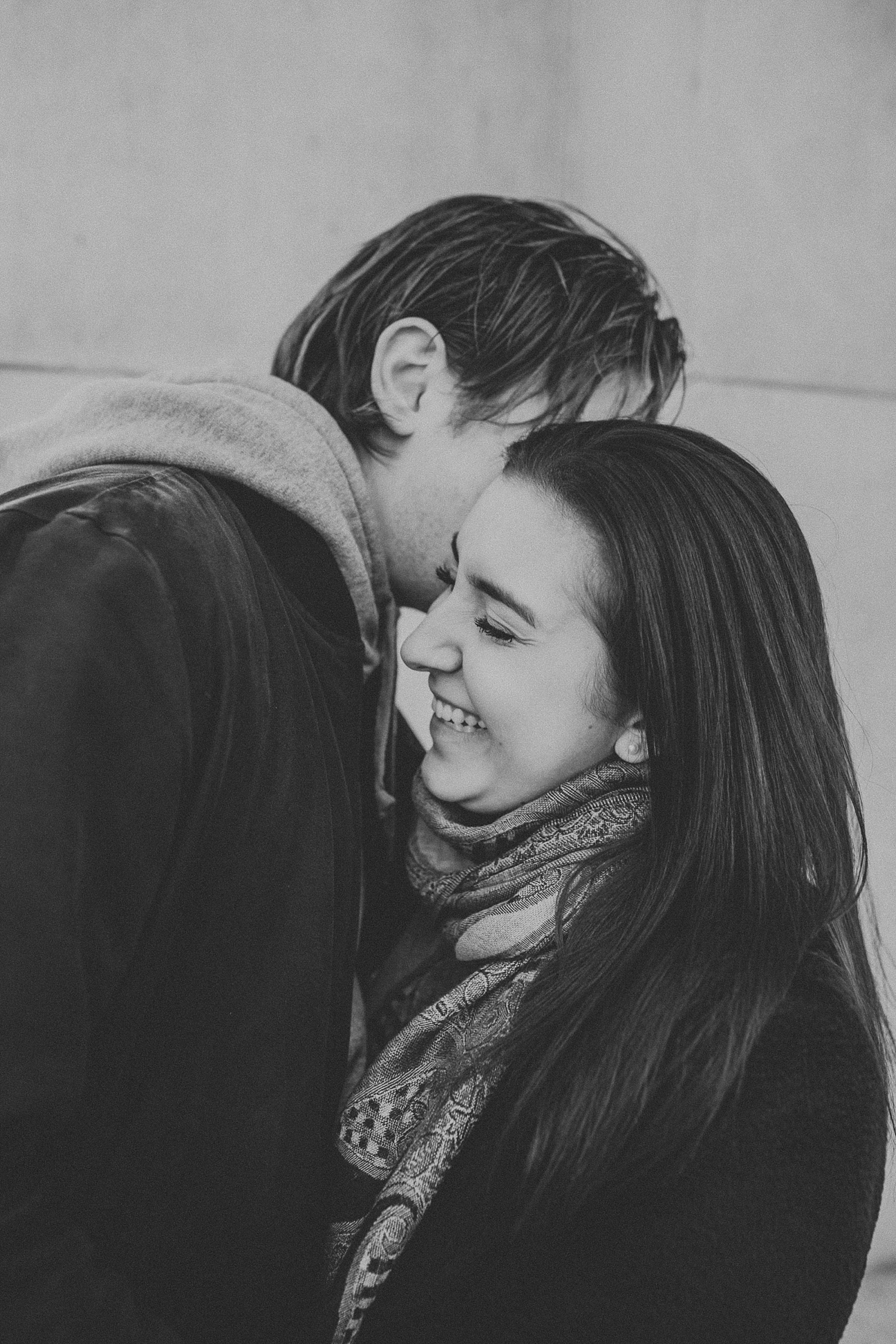 Boy whispering secrets into girls ear and giggling during engagement session in New York City, New York