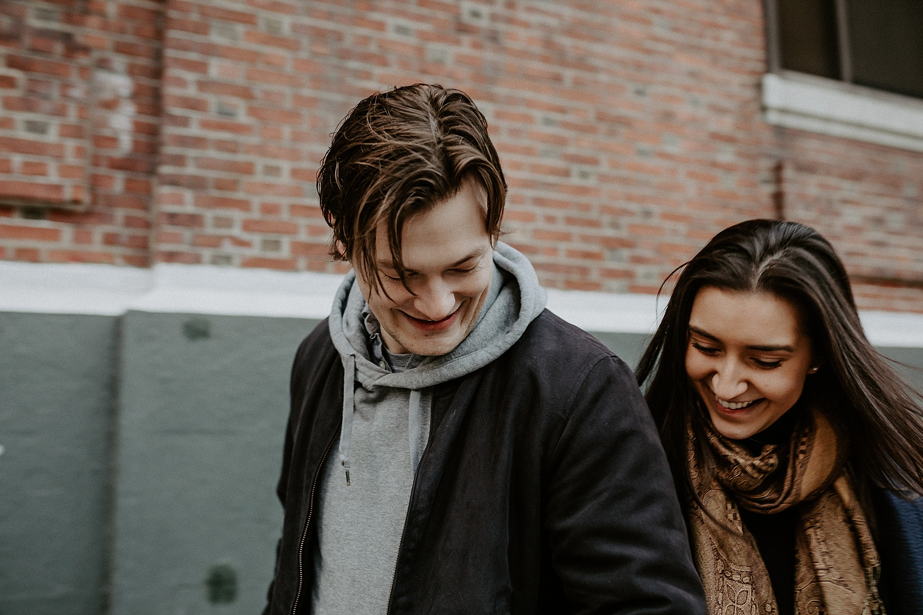 Couple having a sweet and fun moment bumping into one another during engagement session in New York City, New York