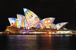 The Sydney Opera House with a cultural projection on its usually-white facade.