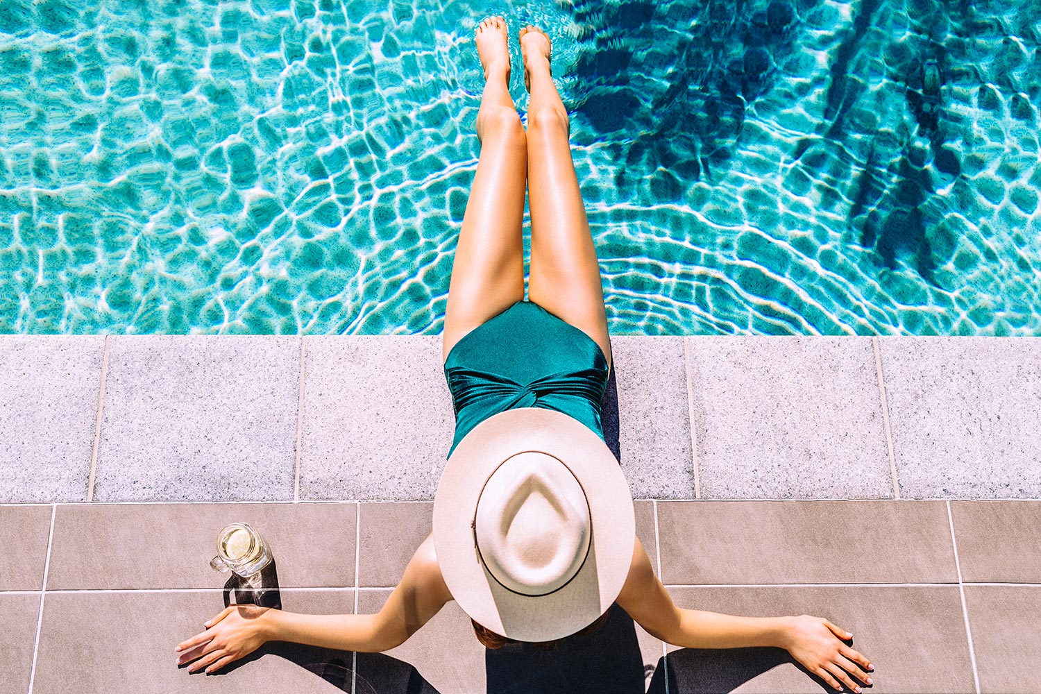 Young woman relaxing by the pool at resort
