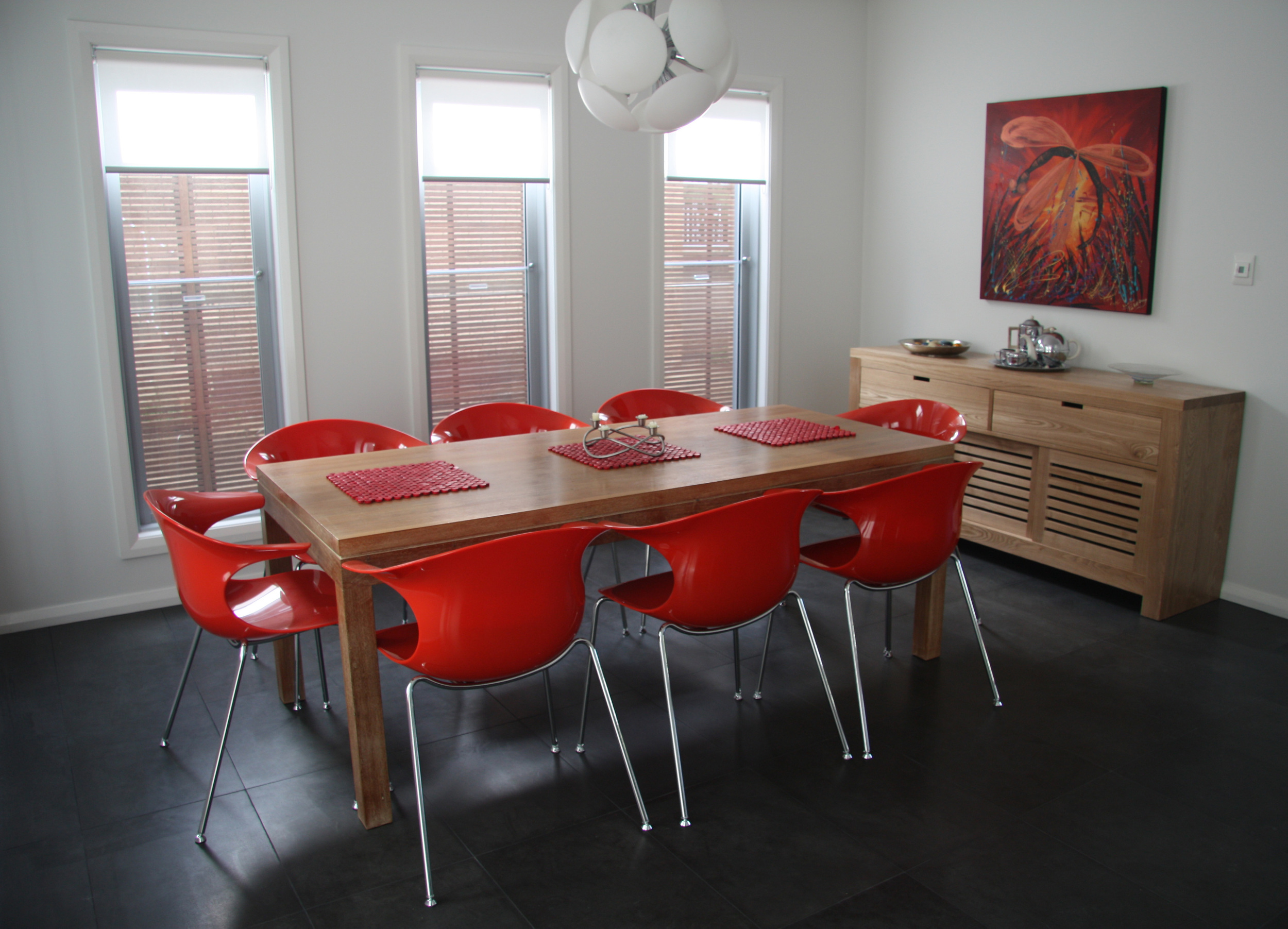 This image is one taken from a beautifully designed home with bluestone throughout - dining room, kitchen, living room and hallway.The result is stunning bright colours e.g. red being used to contrast the formality of the dark grey bluestone.