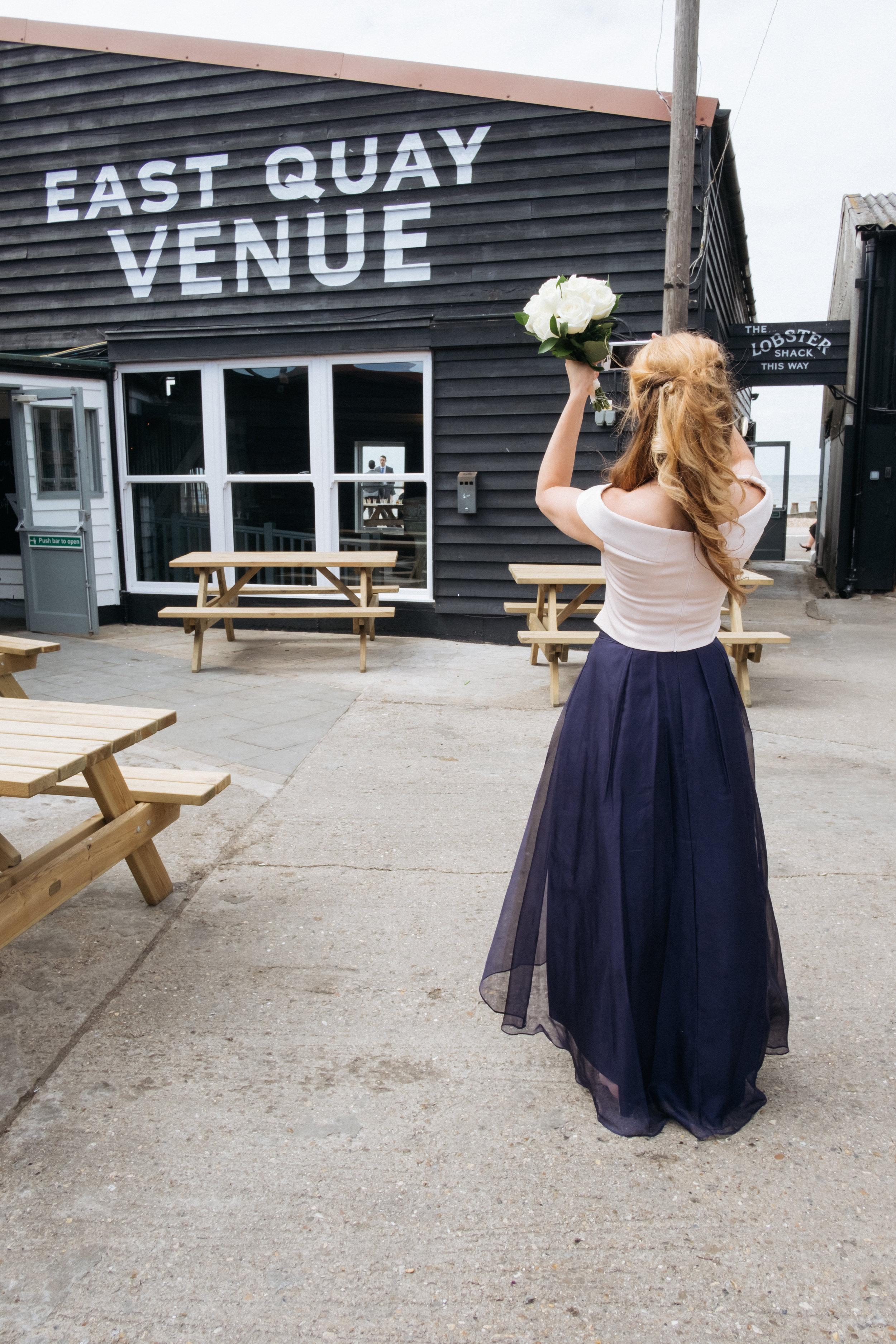 Bridesmaid taking photograph at East Quay wedding