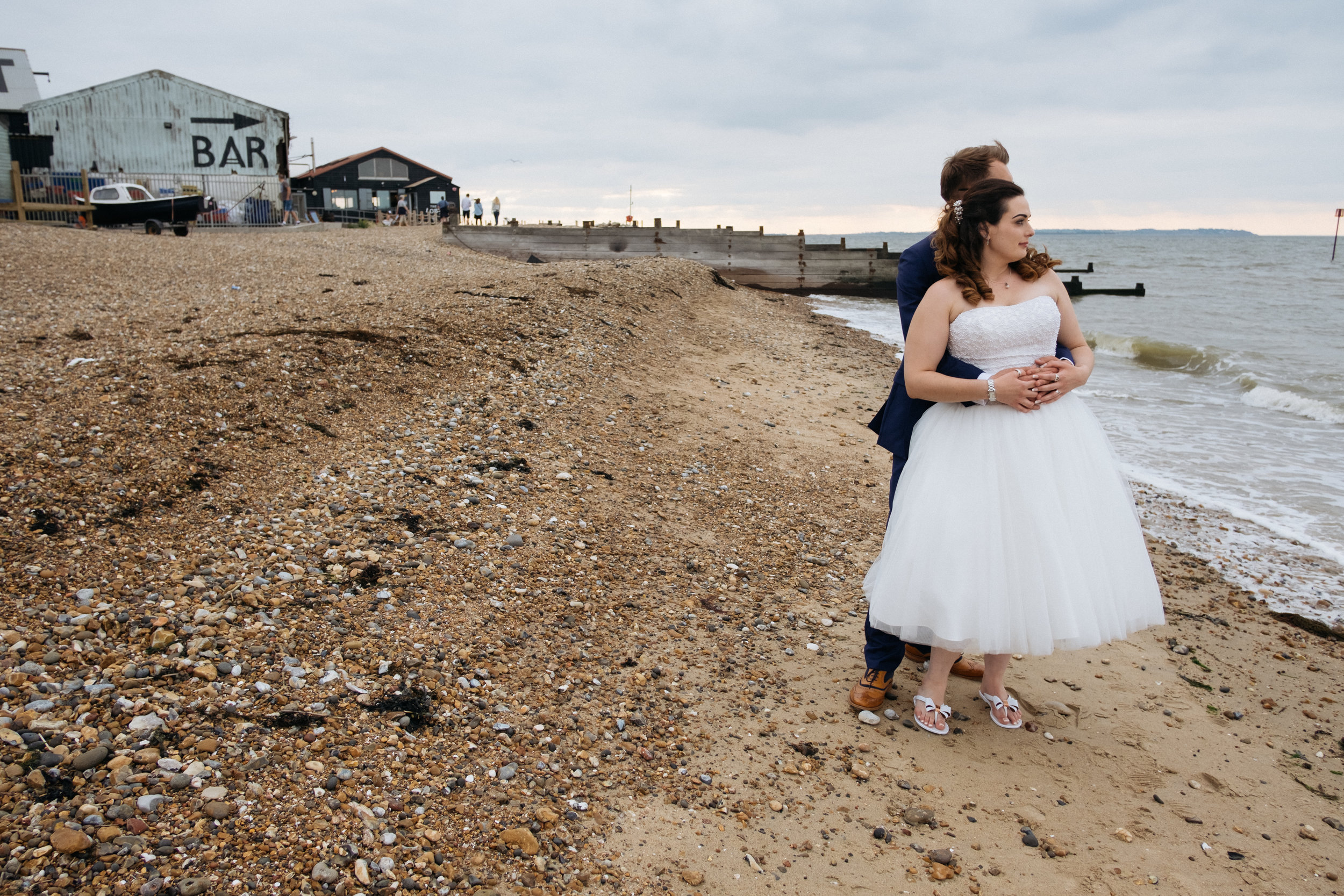Bride and groom on the beach in Whitstable outside East Quay wedding venue