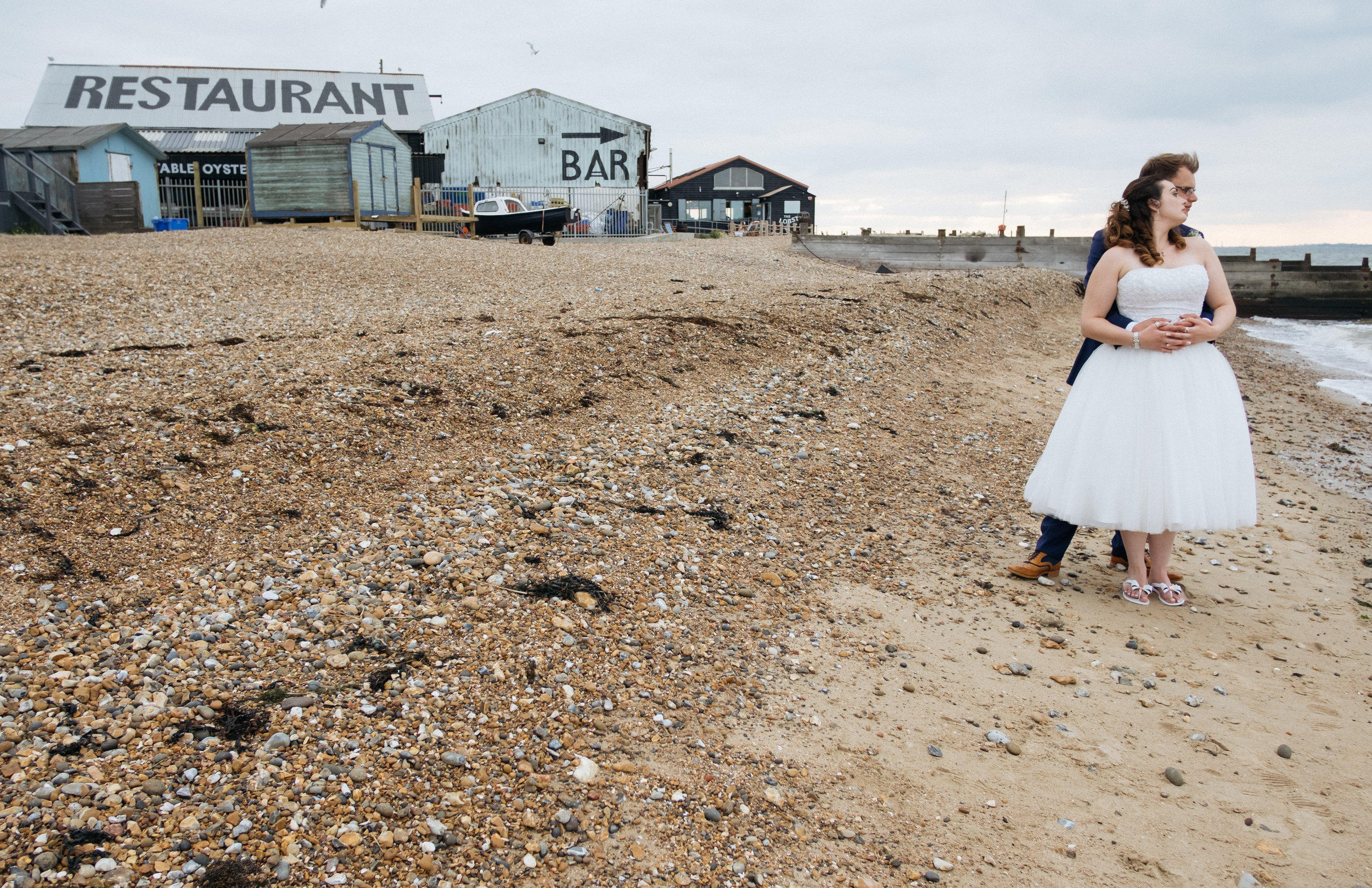 Bride and groom on Whitstable beach outside East Quay wedding venue