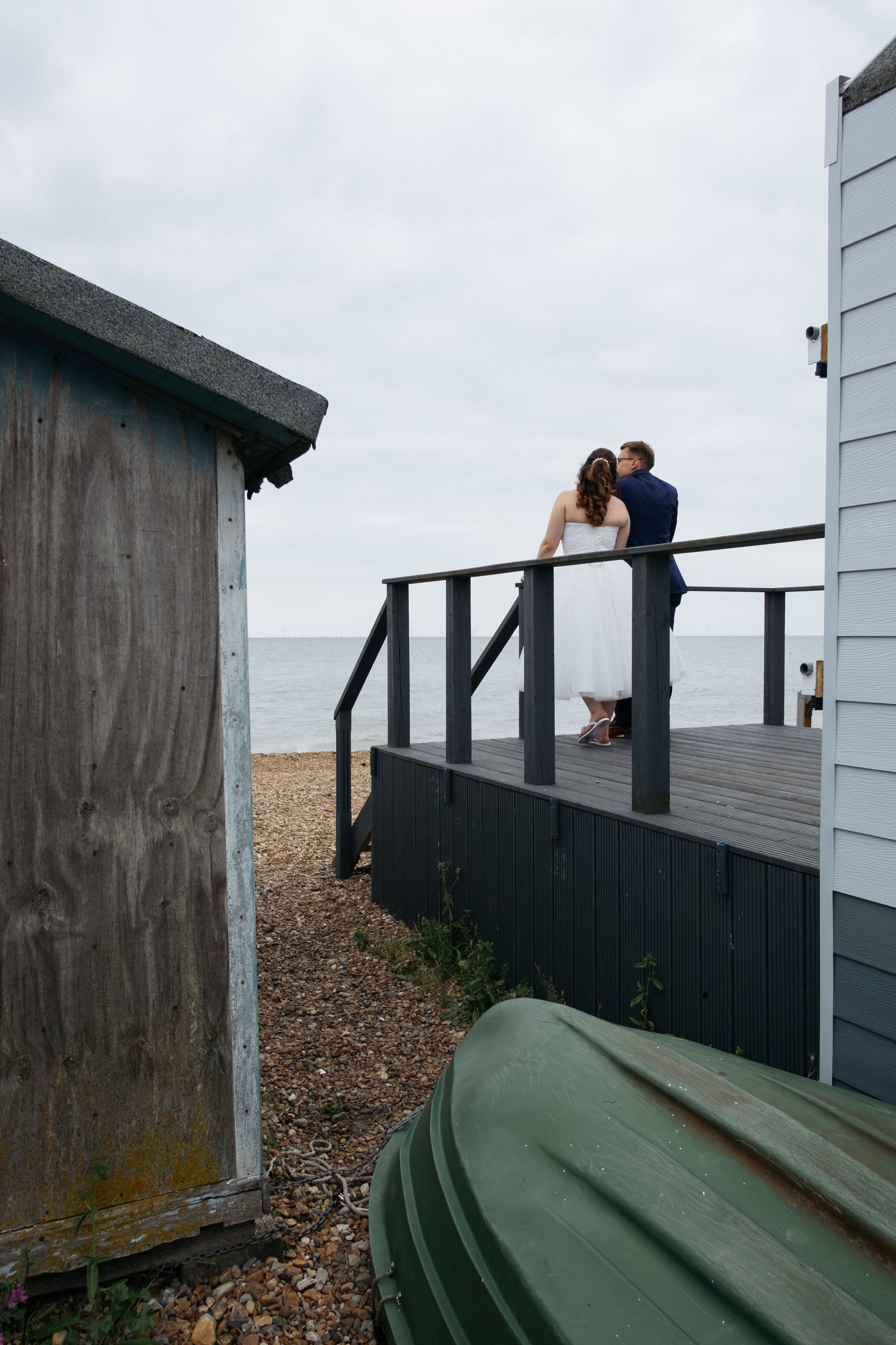 Bride and groom stood by beach hut at East Quay wedding venue