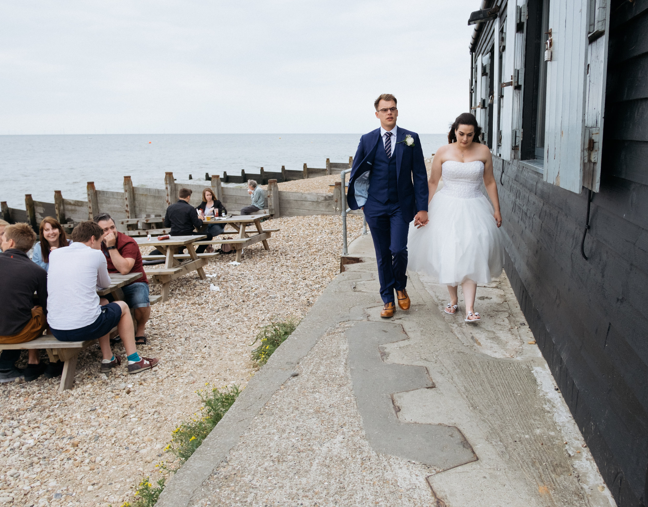 Bride and groom walking along the beach at East Quay wedding venue