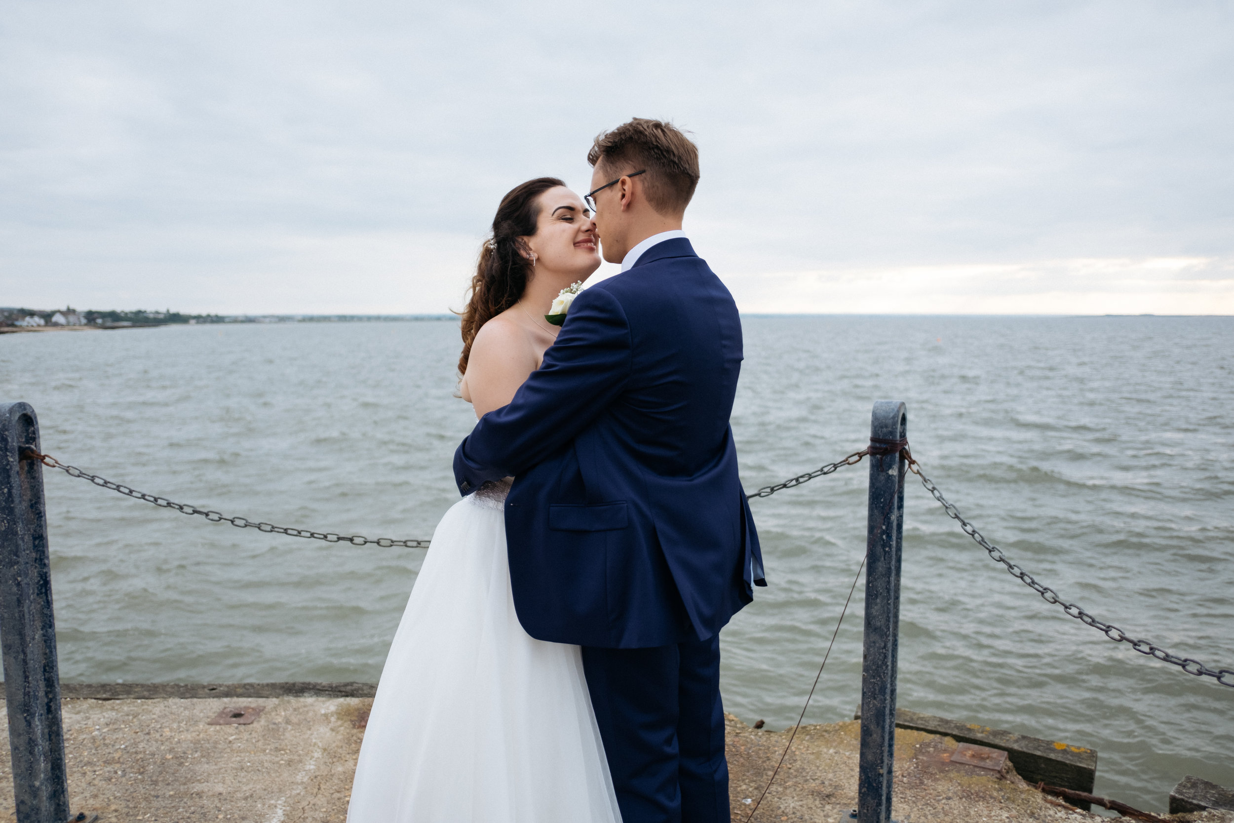 Bride and groom cuddling on Whitstable pier