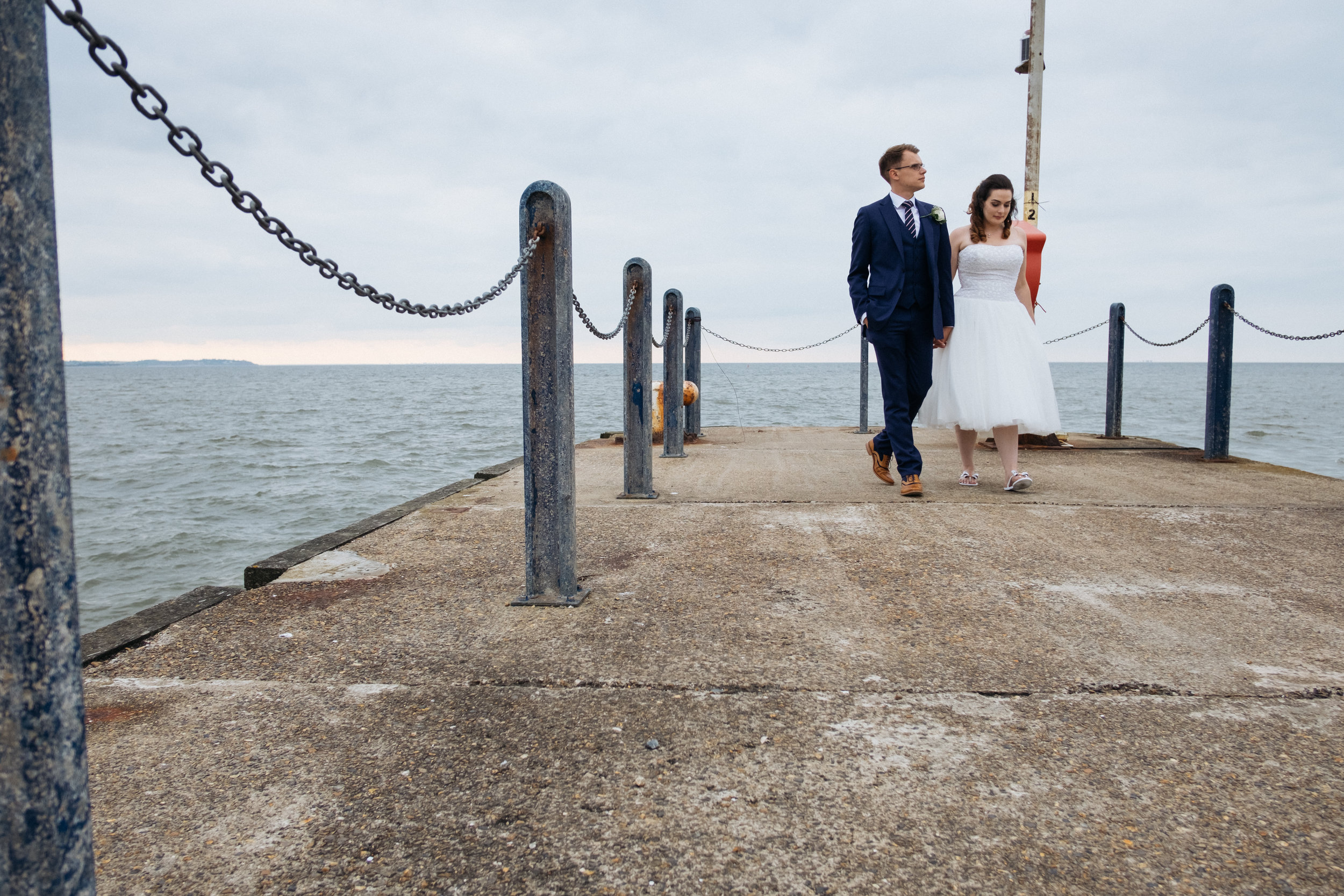 Bride and groom walking on Whitstable pier