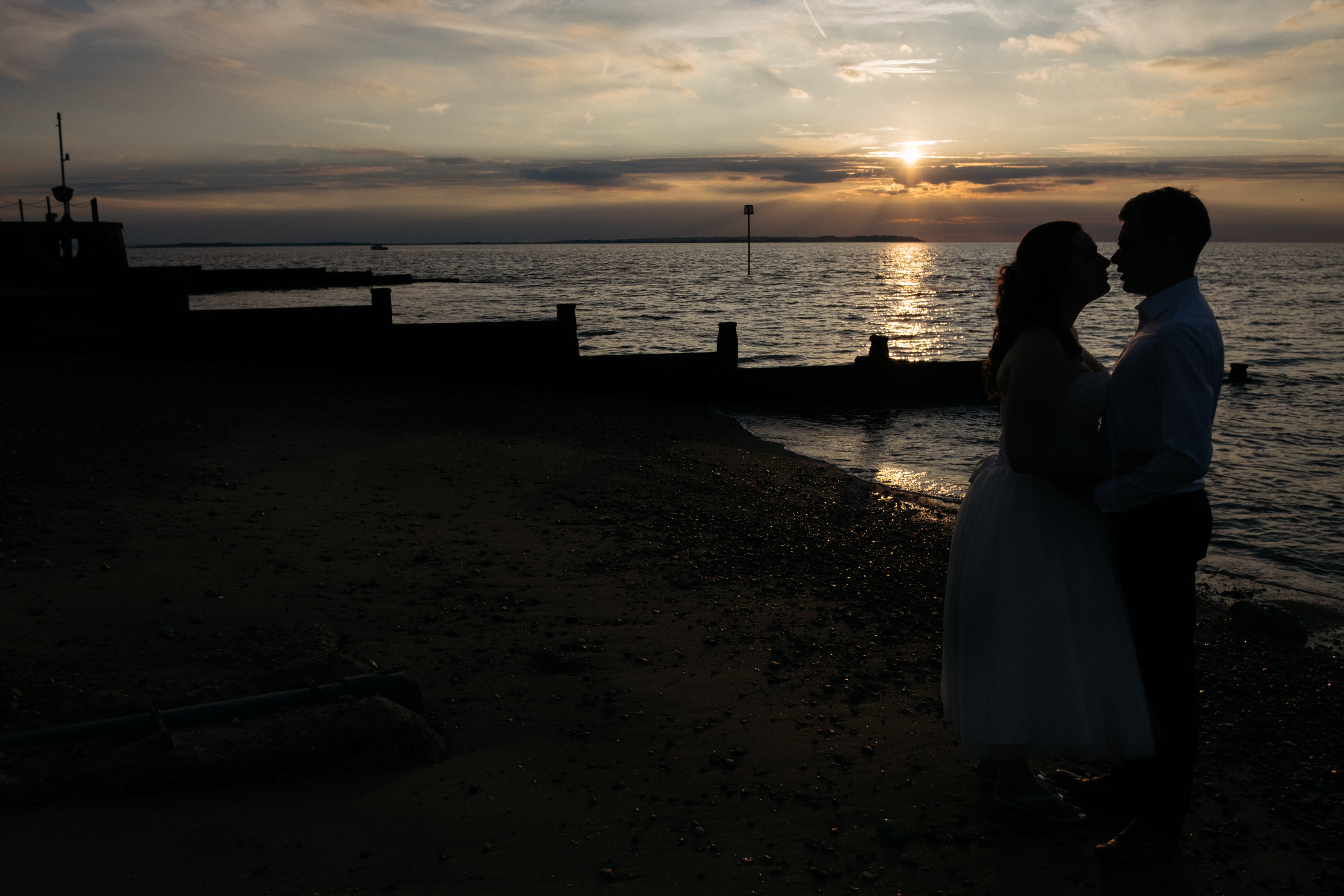 Bride and groom on Whitstable beach at sunset outside East Quay wedding venue