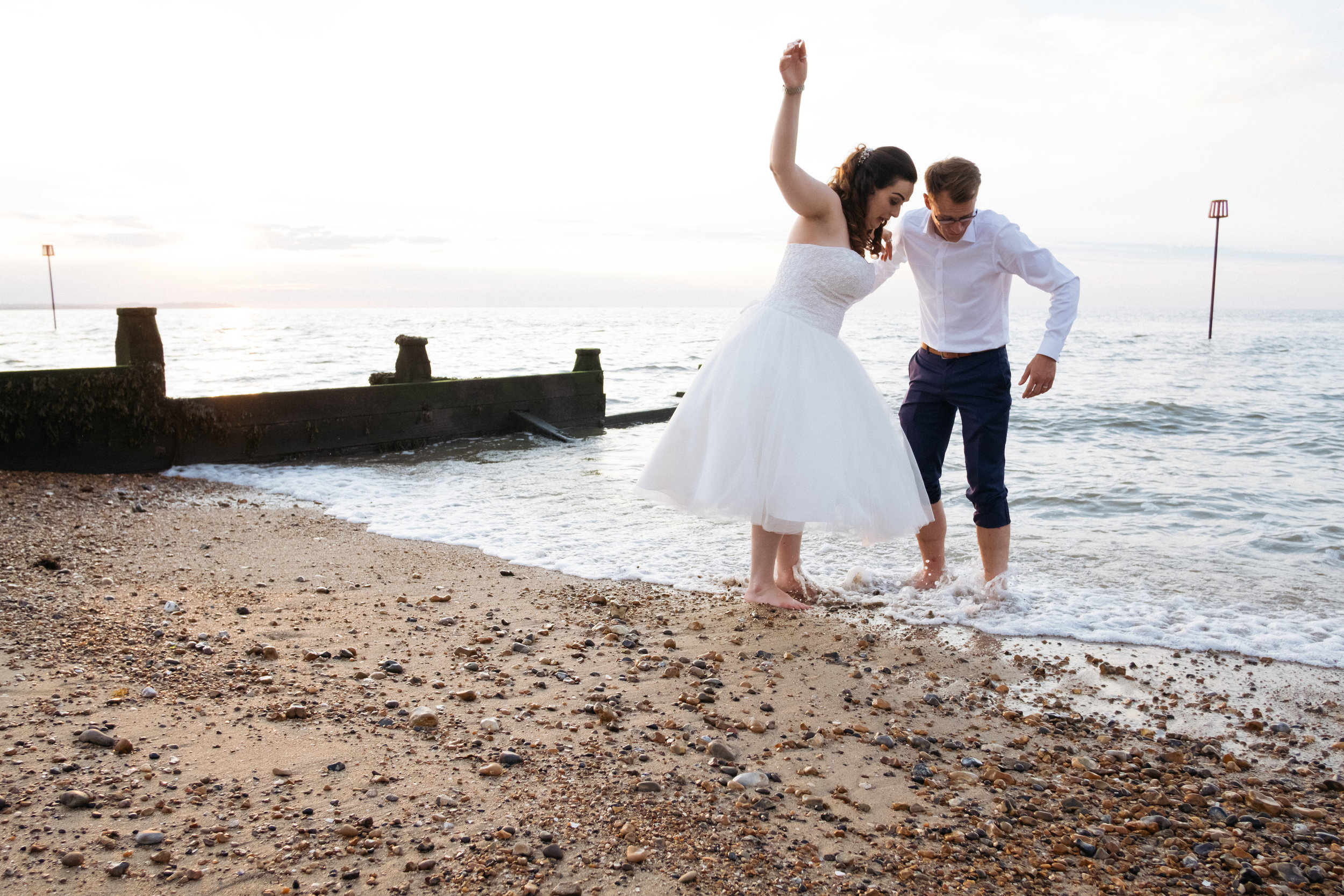 Bride and groom playing in the sea outside East Quay wedding venue