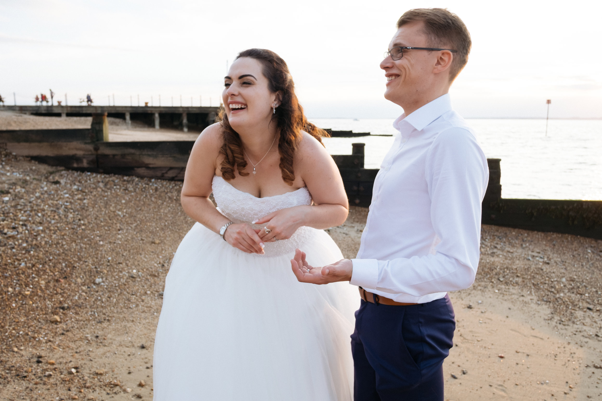 Bride and groom laughing on the beach outside East Quay wedding venue
