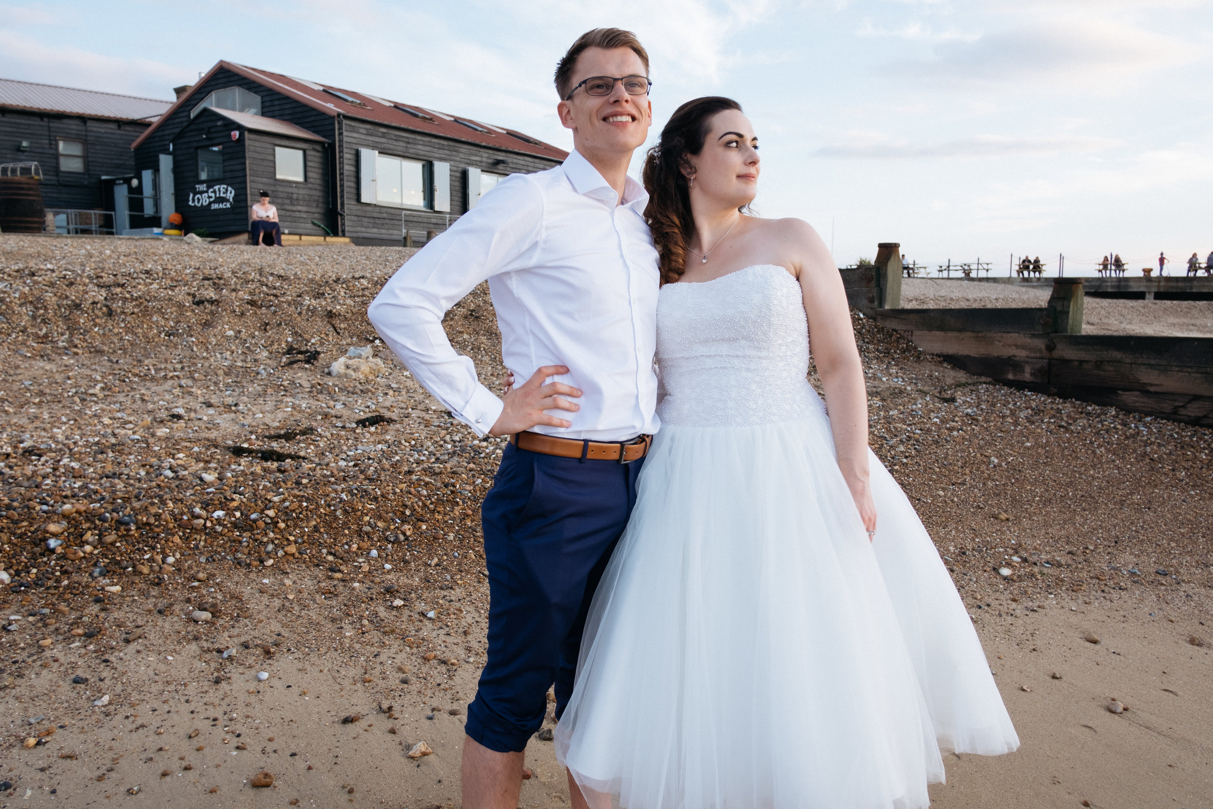 Bride and groom stood on Whitstable beach outside East Quay wedding venue