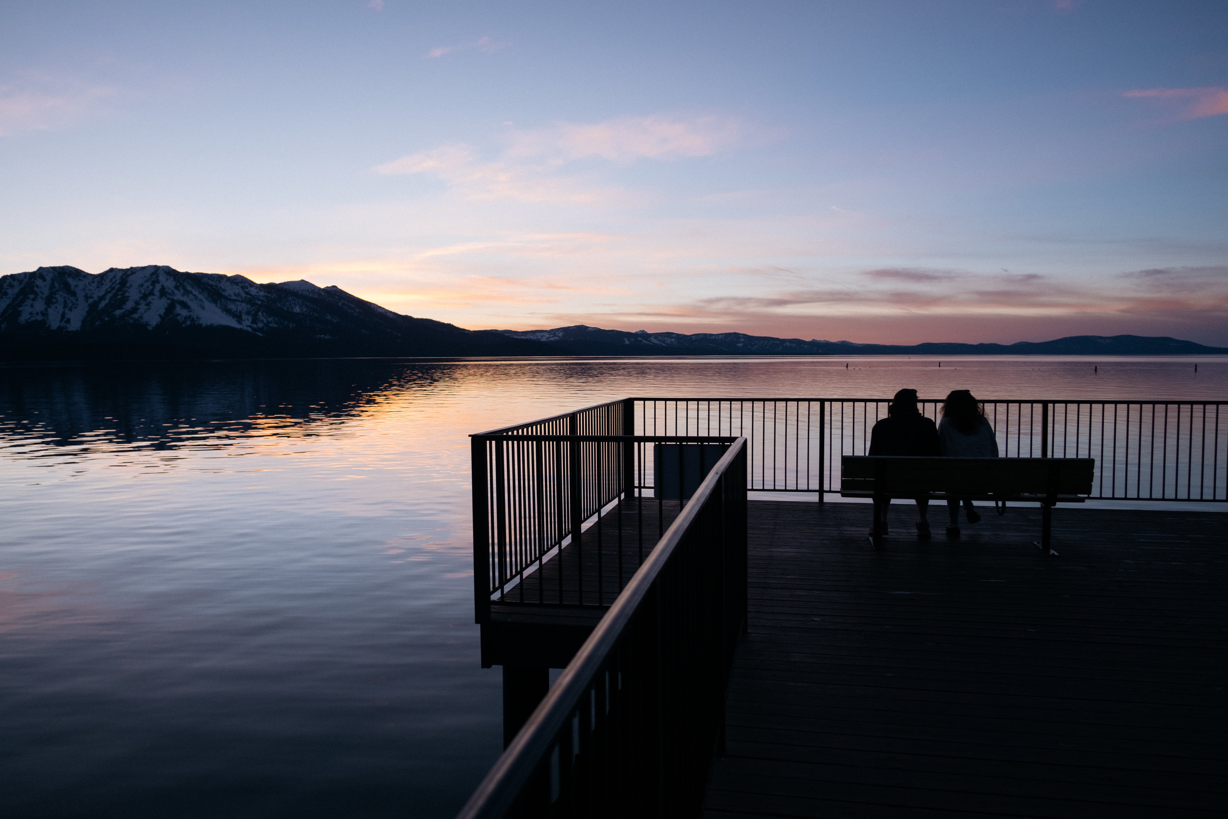 A couple watching the sunset above Lake Tahoe