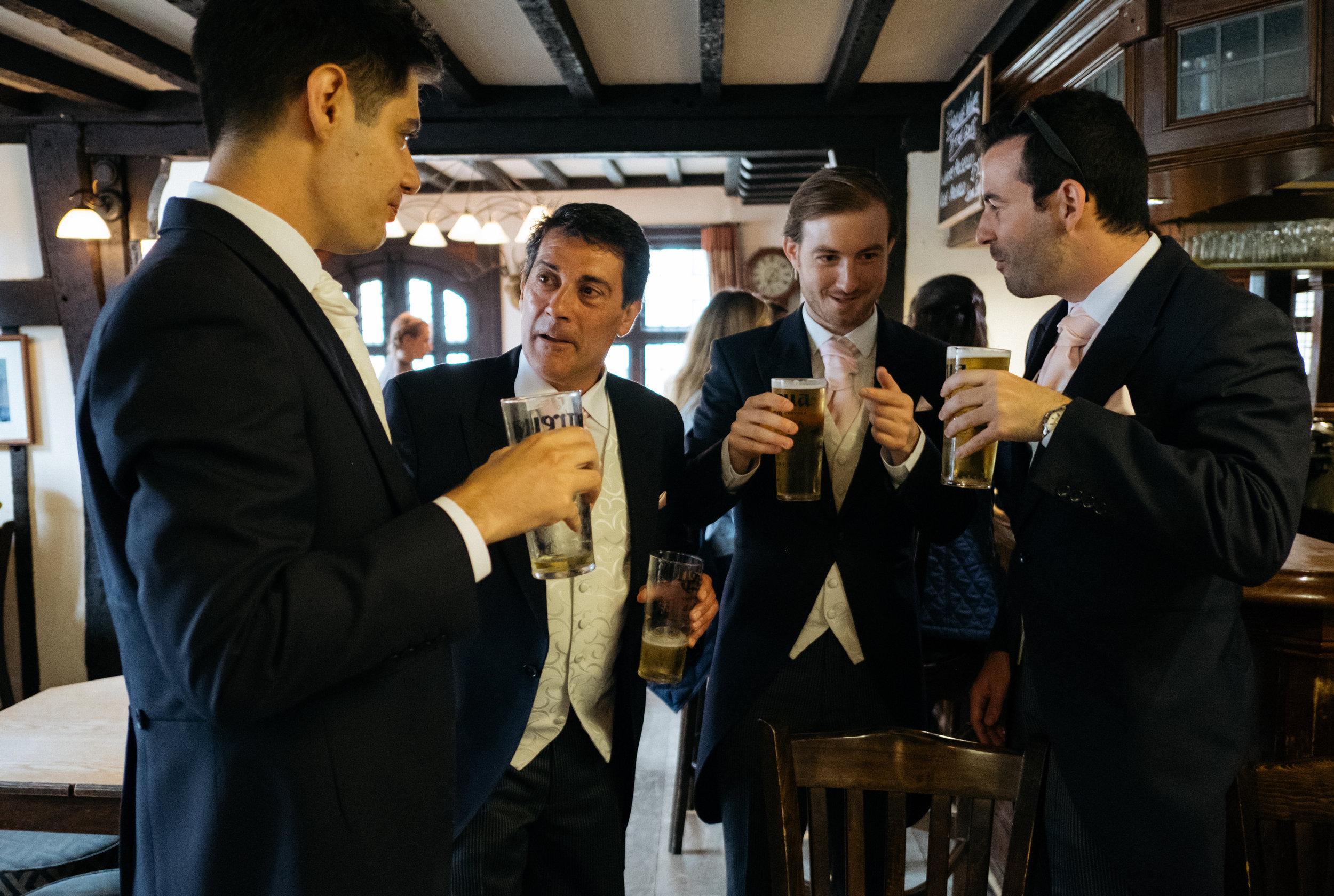 Groom and groomsmen sharing a pint of beer