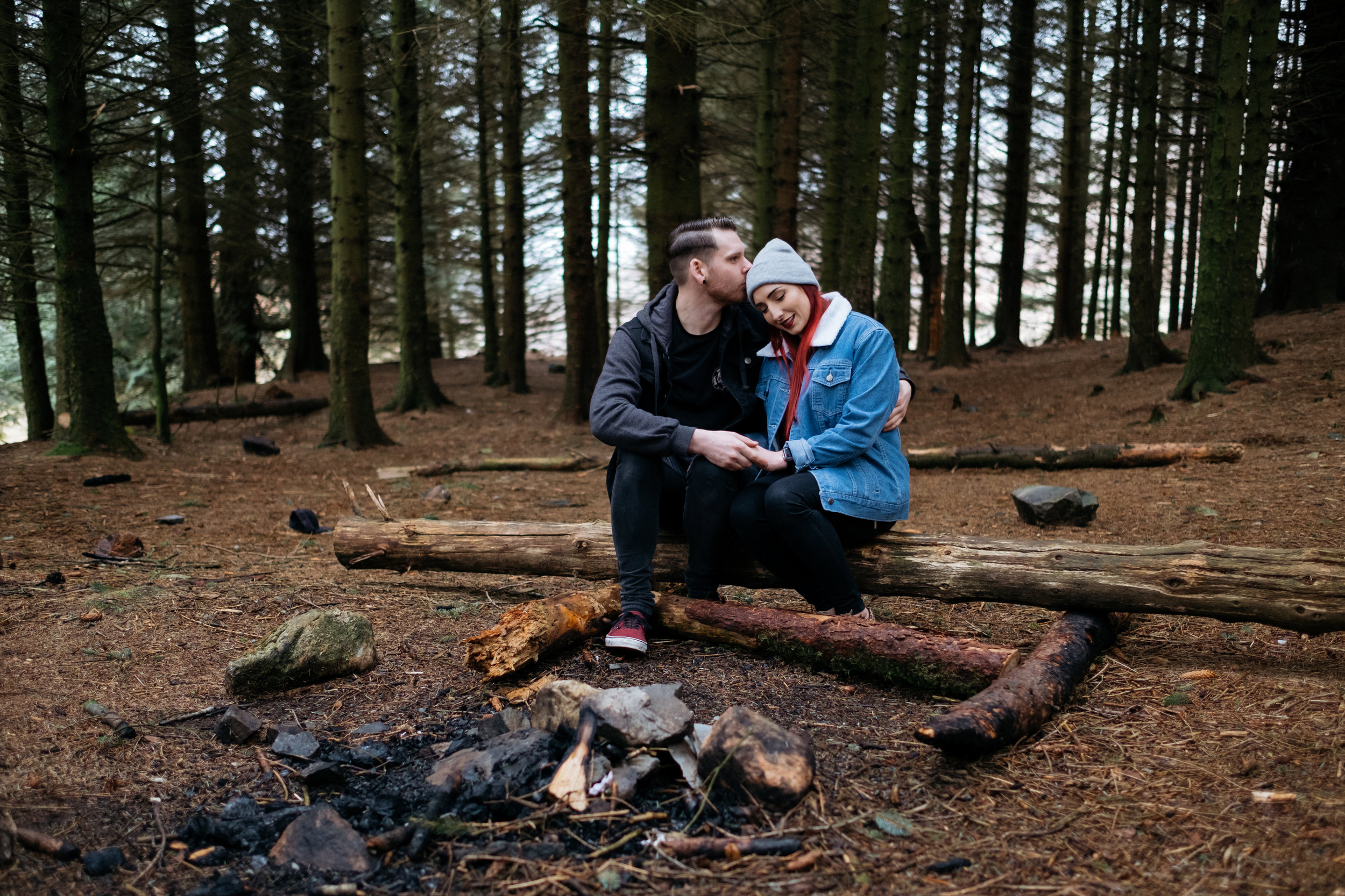 Cute couple sat around a campfire