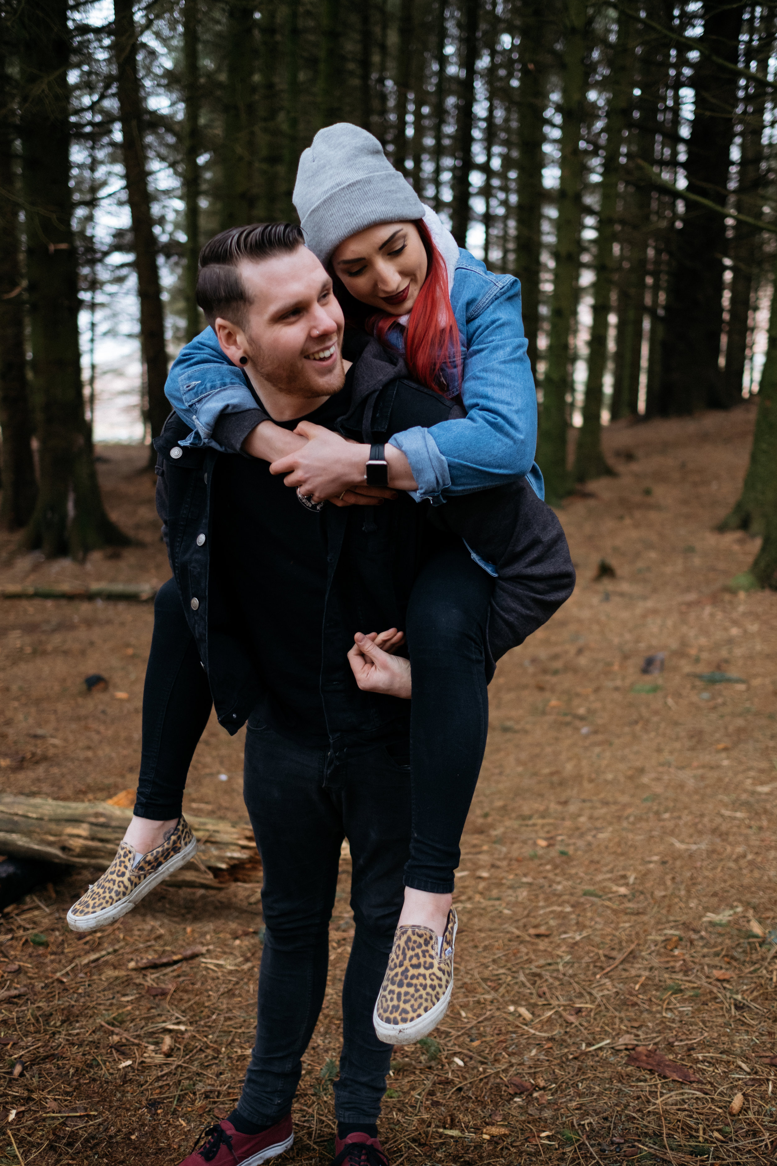 Piggybacks in the woods engagement photography in the Lake District